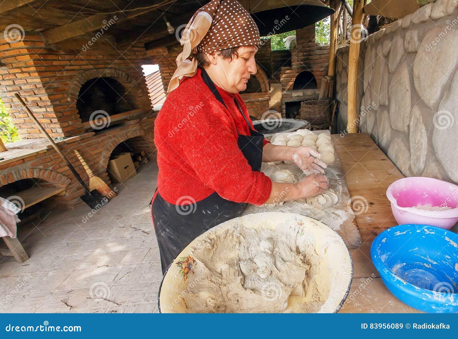 资深妇女烘烤饼在她的英王乔治一世至三世时期村庄样式的家庭厨房里与石烤箱