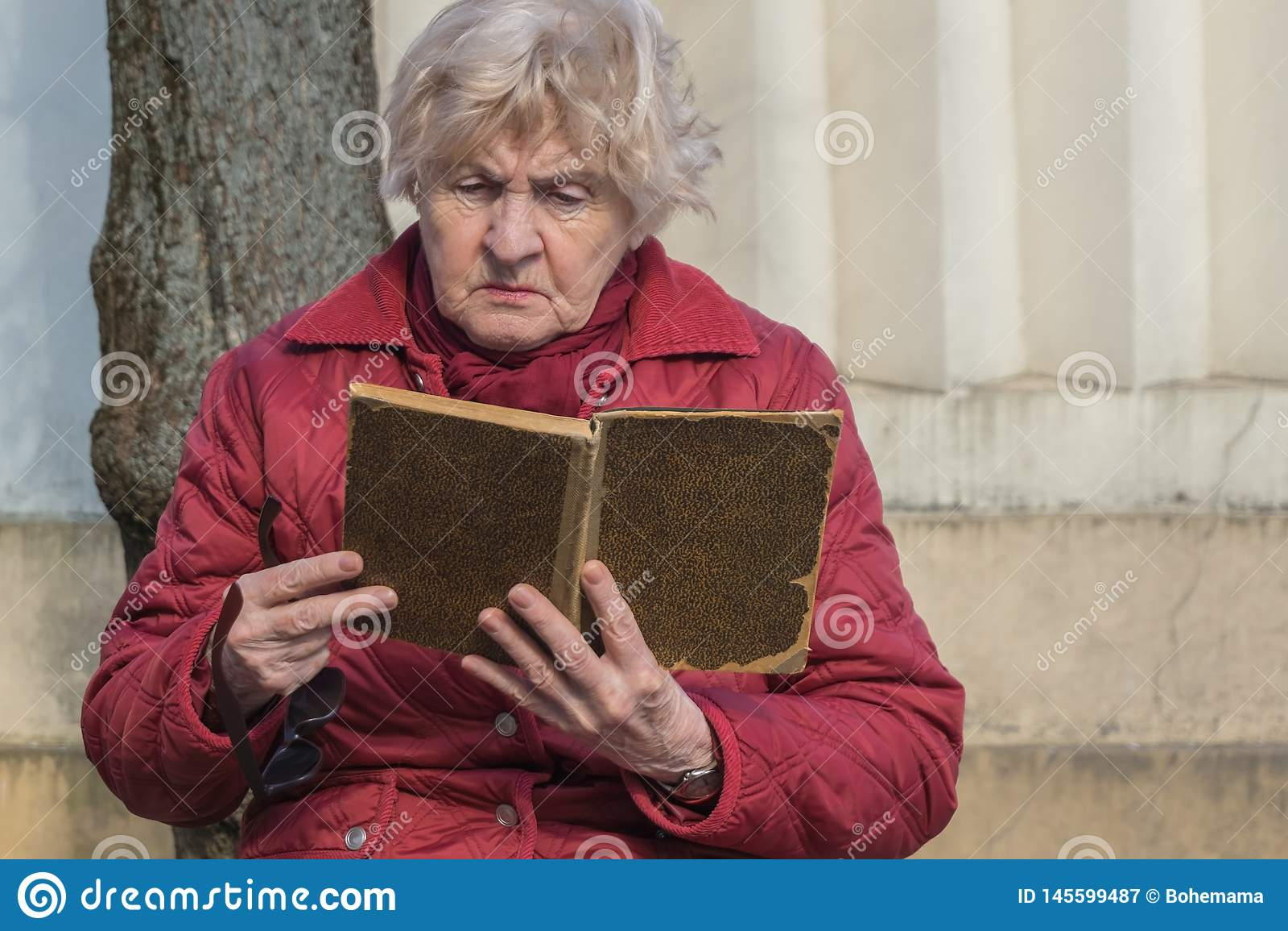资深妇女藏品书在她的手上和读书在公园