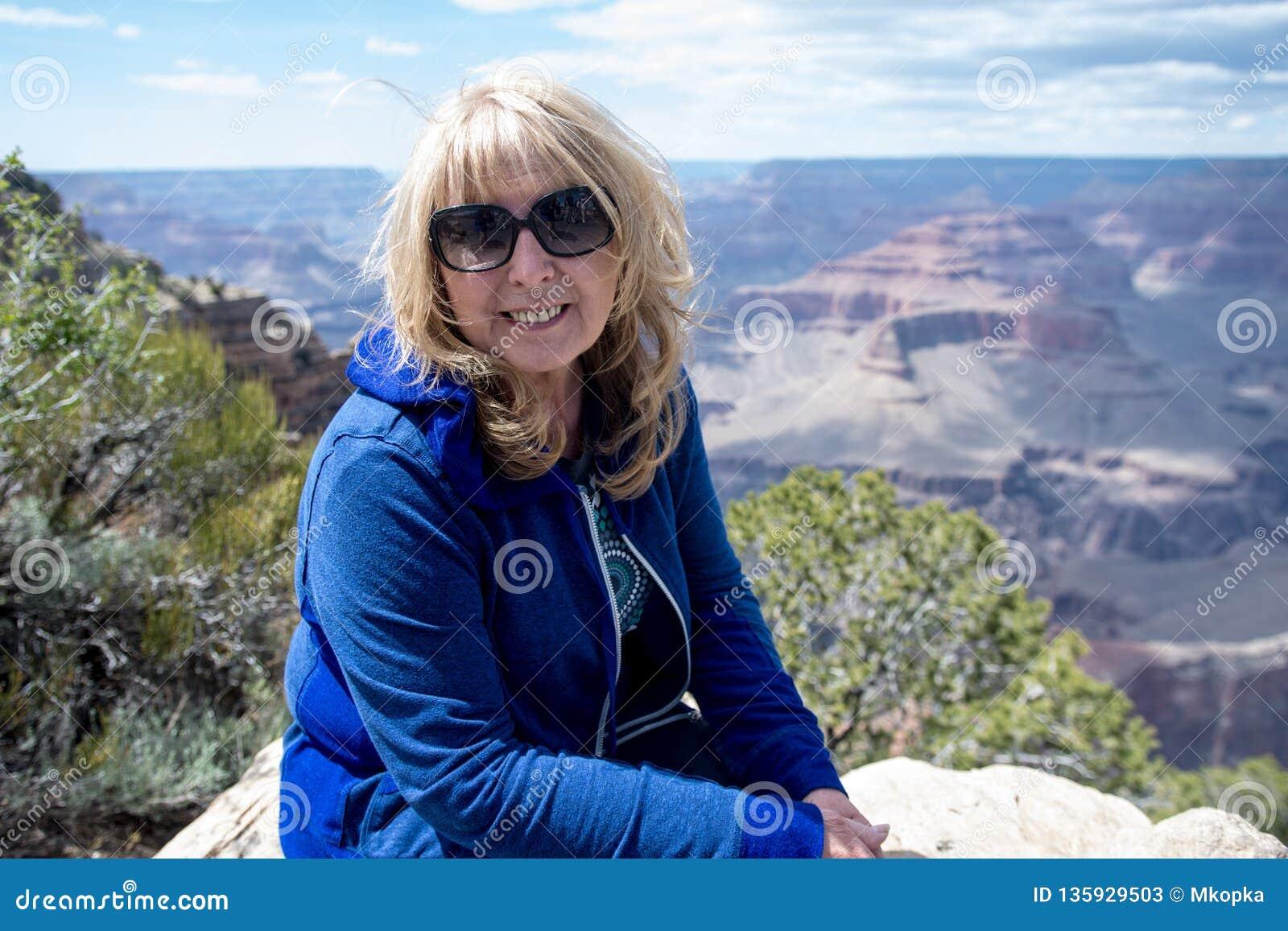 资深妇女60s坐并且摆在沿大峡谷国家公园的南外缘的一个观点,当在度假时