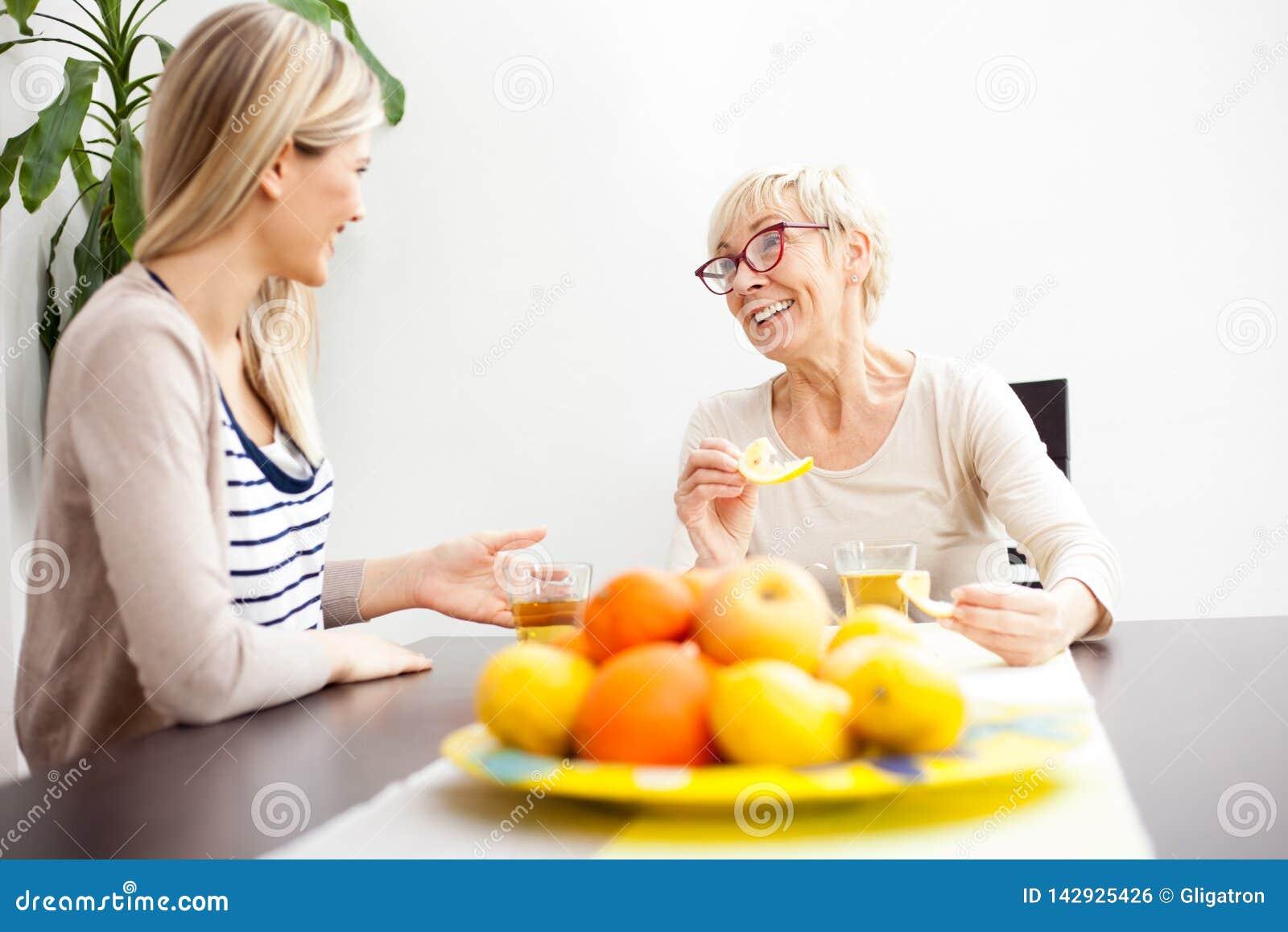 资深母亲和女儿谈的和饮用的茶在明亮地被点燃的餐厅