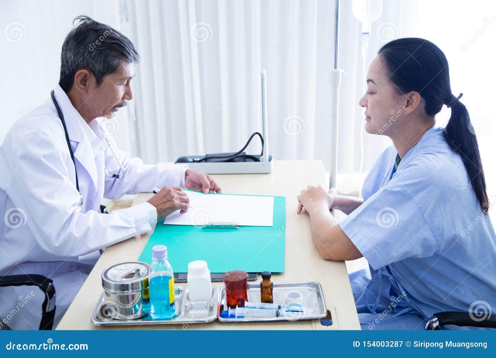 资深男性医生微笑谈论与讲话与他的资深患者