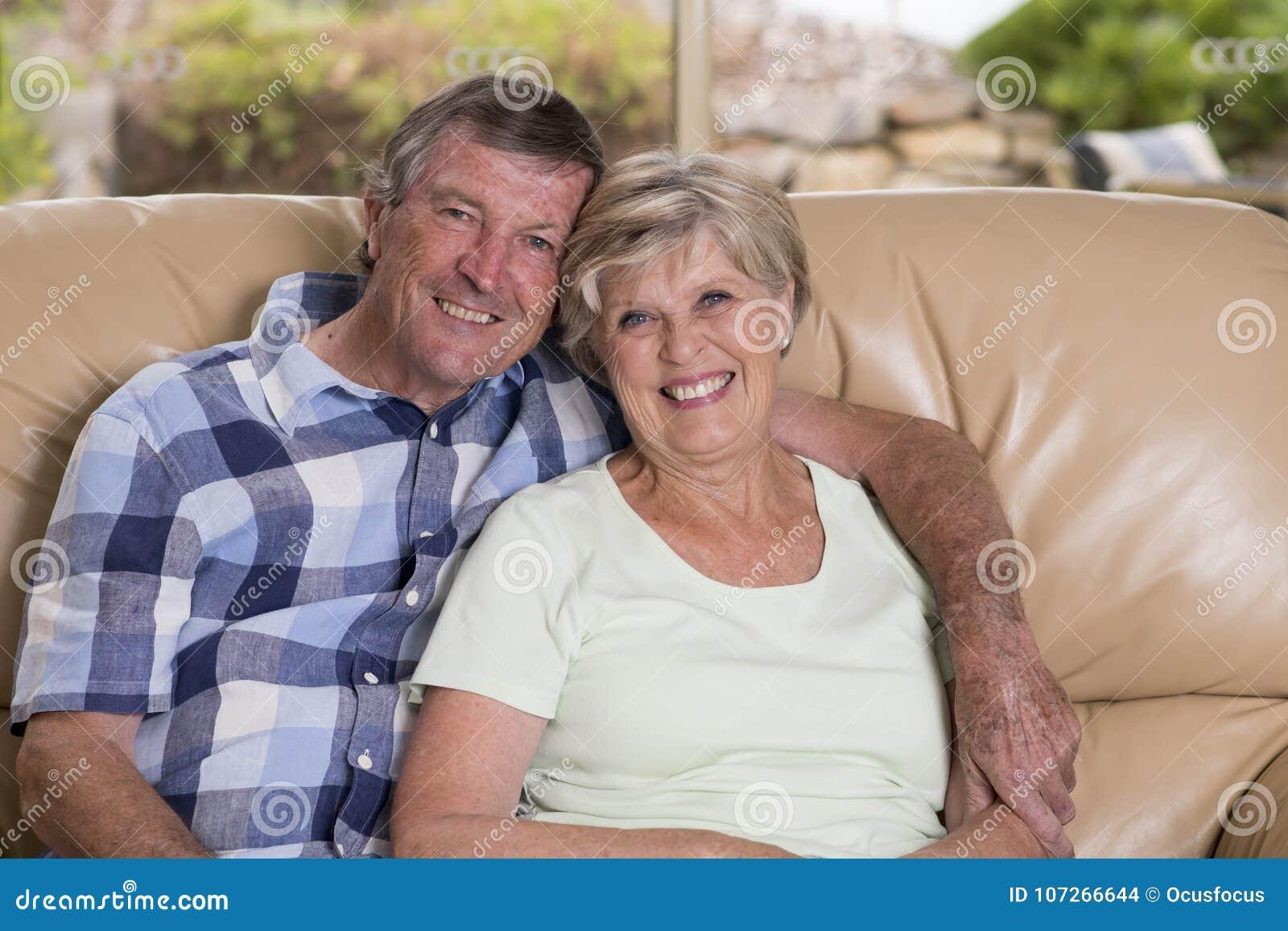 资深美好的中年夫妇大约70岁看起来微笑的愉快的一起在家客厅沙发的长沙发甜在生活中