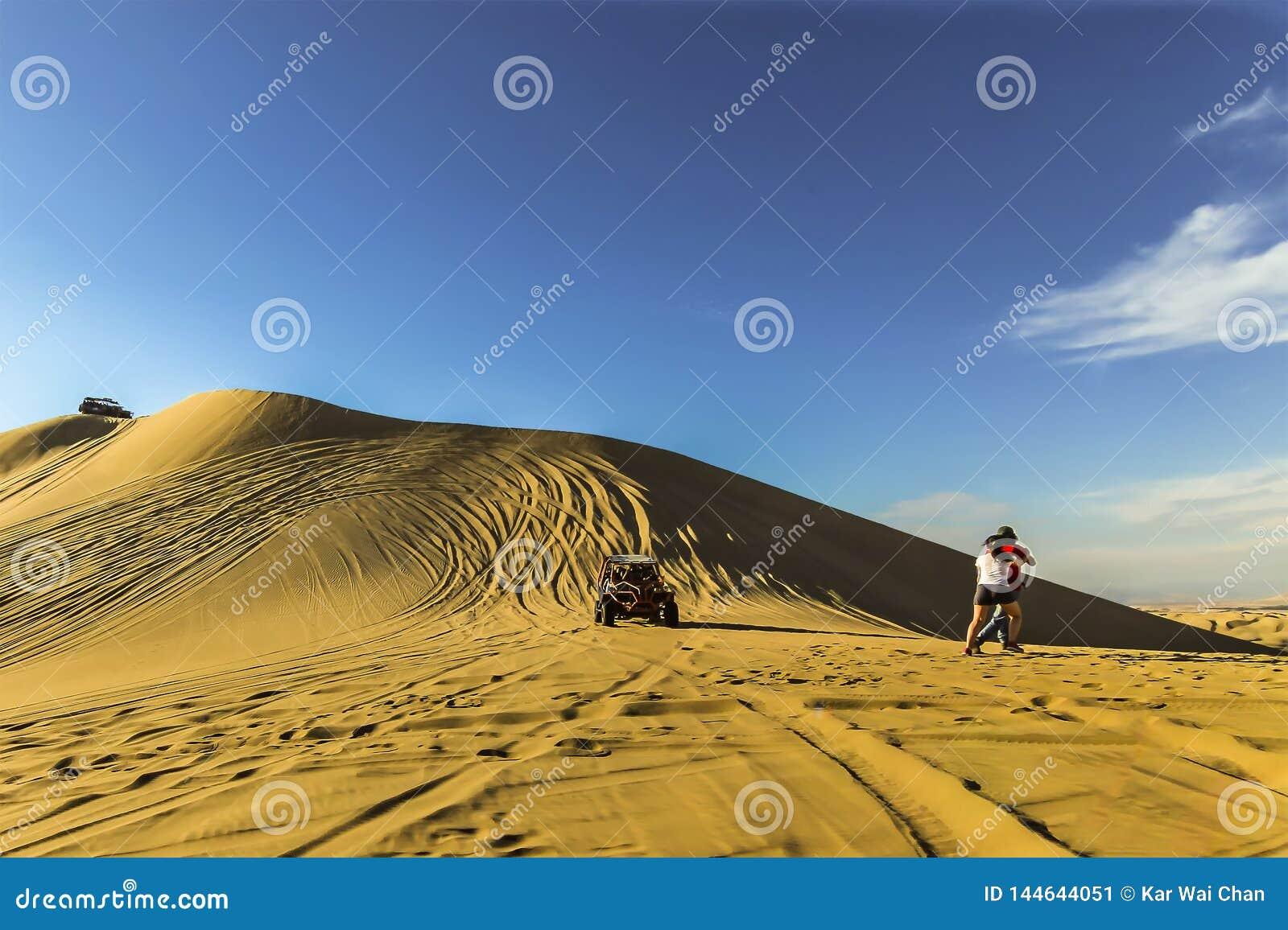 赛跑在倾斜下的沙丘儿童车作为移动的游人在旁边