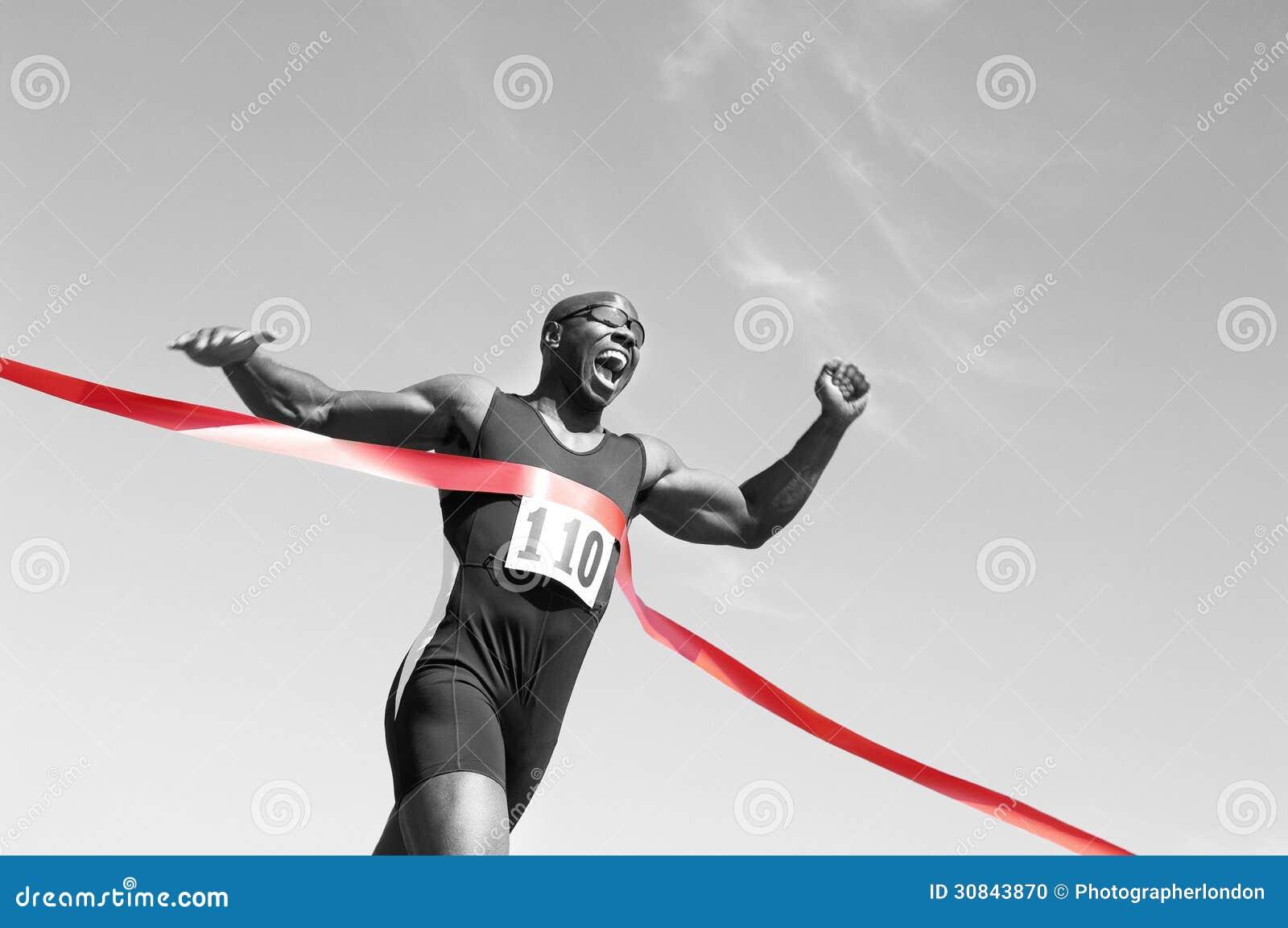 一条非裔美国人的男性赛跑者横穿终点线的低角度视图反对蓝天的.