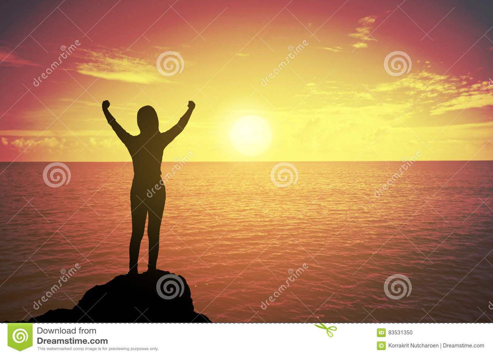 赢取的成功妇女剪影站立和举手的日落或日出的为庆祝被到达山