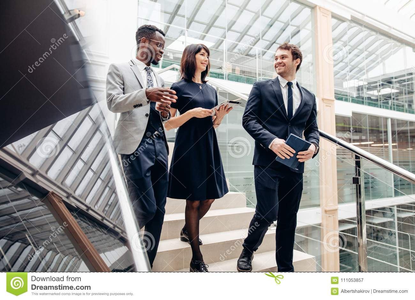 走下来在有数字式片剂的台阶的三个多种族商人