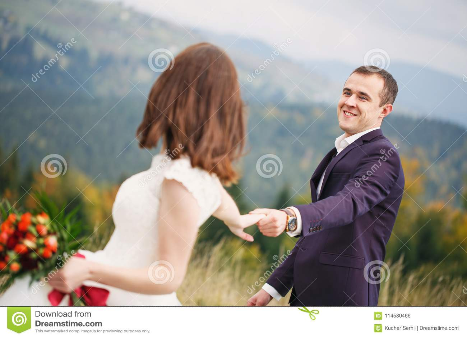 走与山草坪 喀尔巴阡山脉在背景中 新婚佳偶在婚礼之日