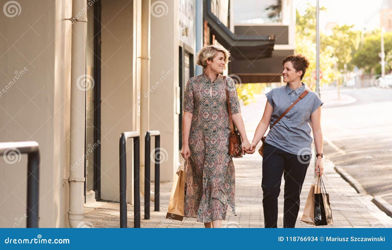 走与购物袋的年轻女同性恋的夫妇在城市