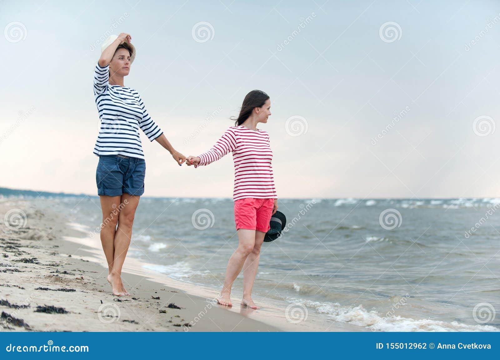 走两的年轻女人结合在一起使在海边的手