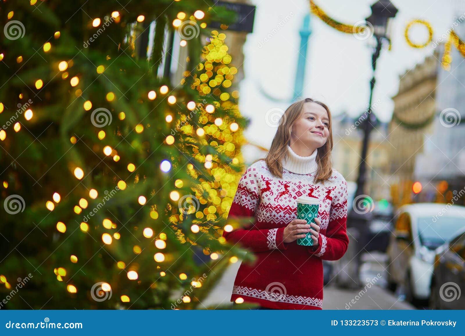 走以热的饮料的女孩去在巴黎街道上为圣诞节装饰了