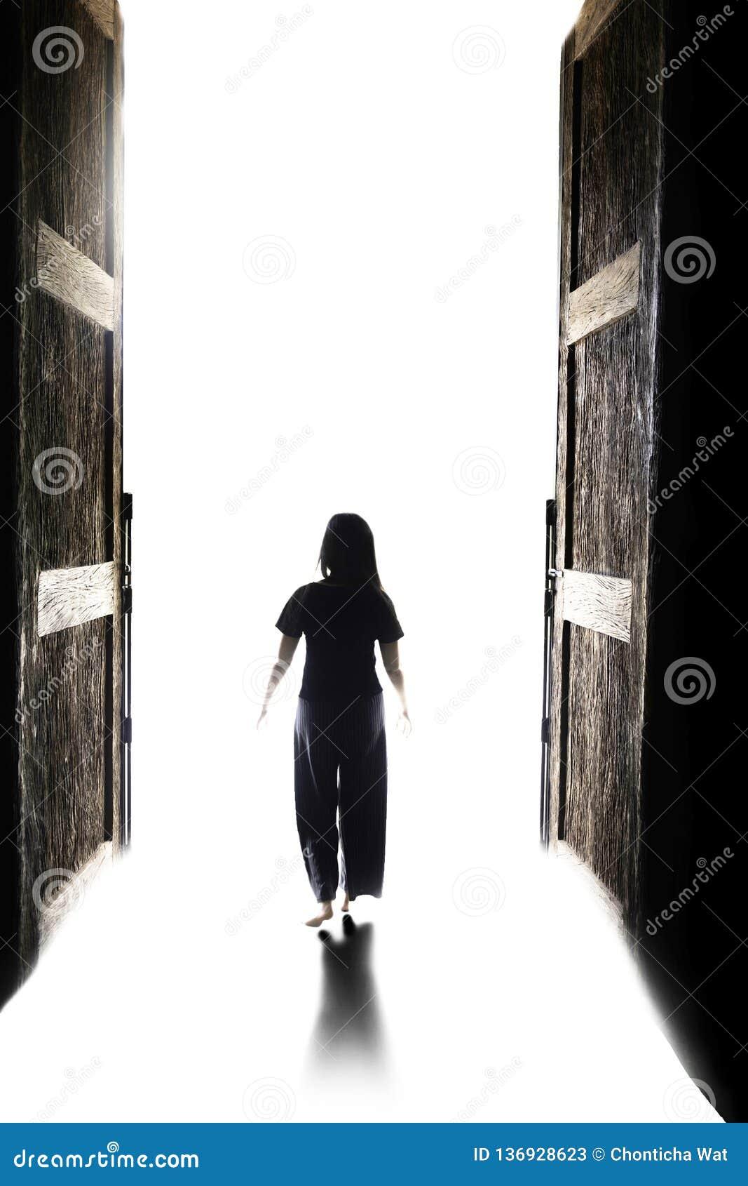 走入光的妇女通过开放大门