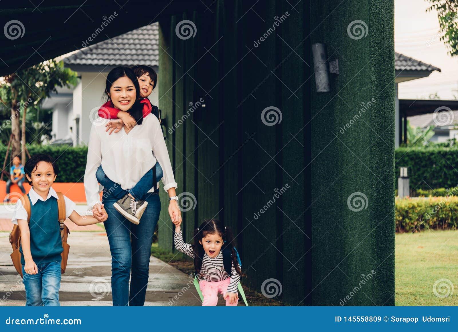走出去从家庭举行的手她的孩子的亚裔愉快的母亲