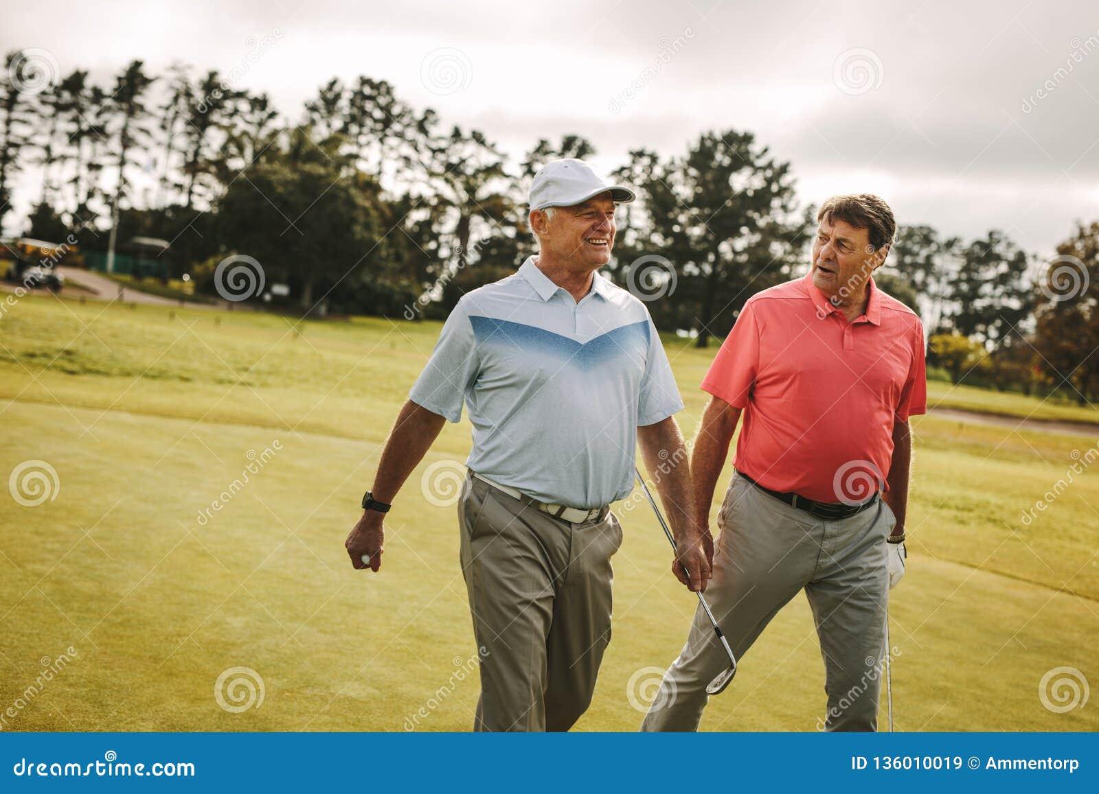 走到下个孔的资深高尔夫球运动员