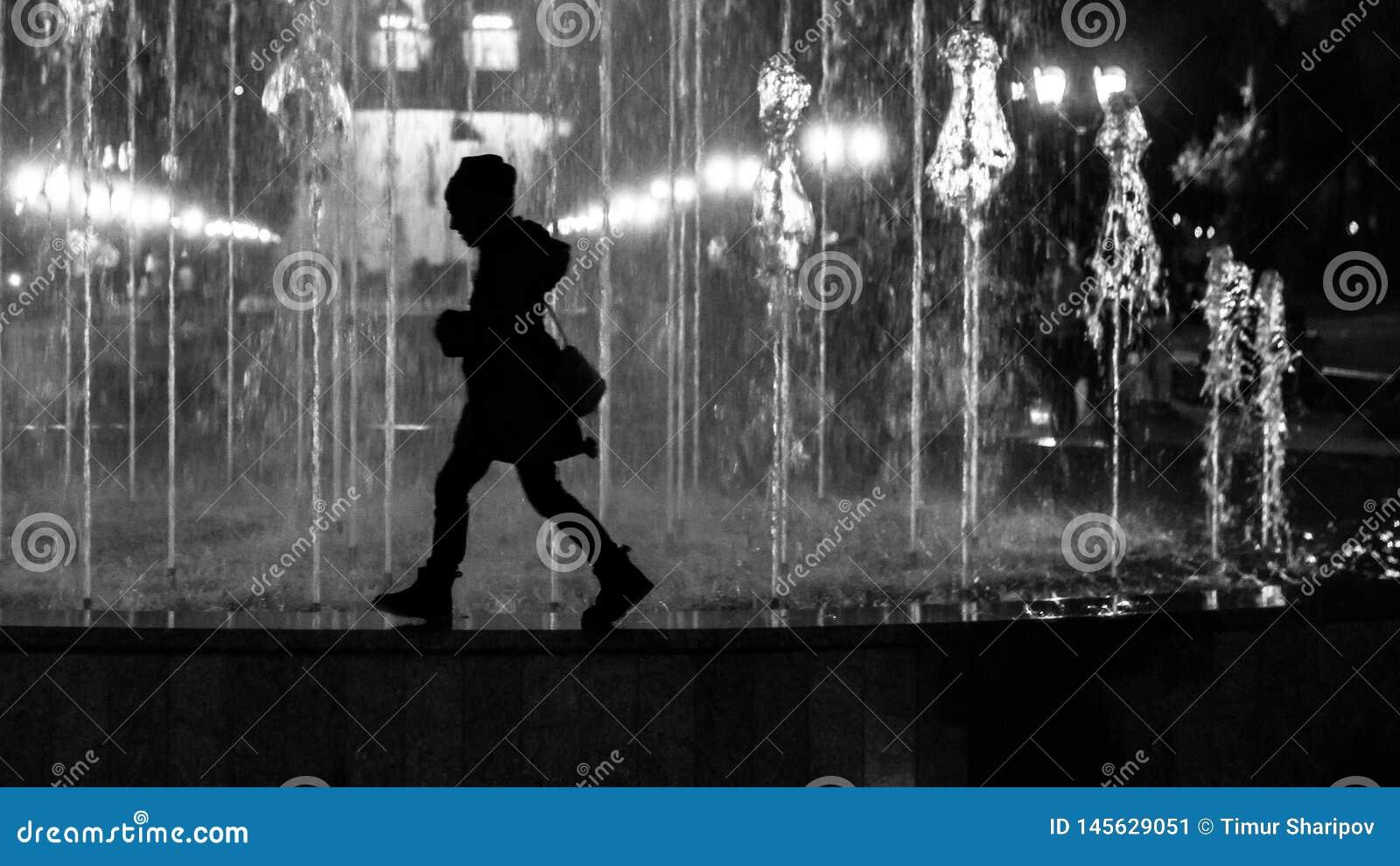 走喷泉边界的小孩子女孩 传统化作为黑白剪影