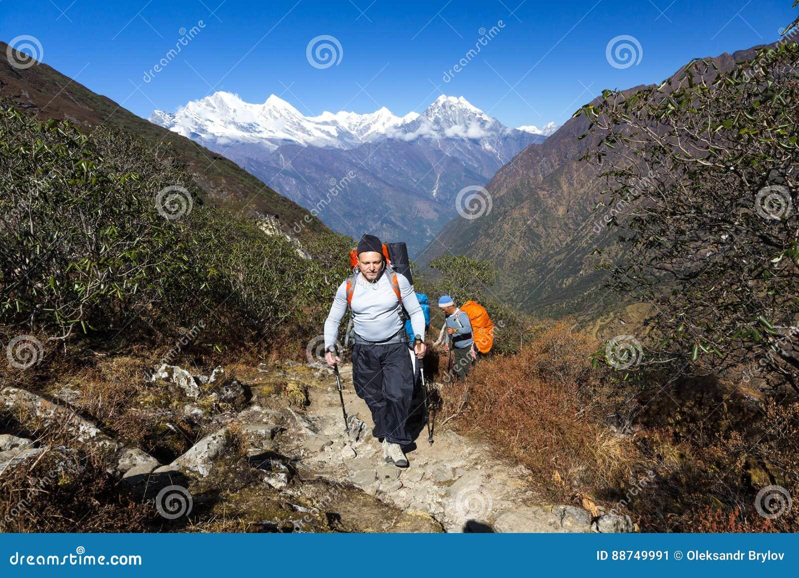 走在与背包的山行迹的年轻远足者