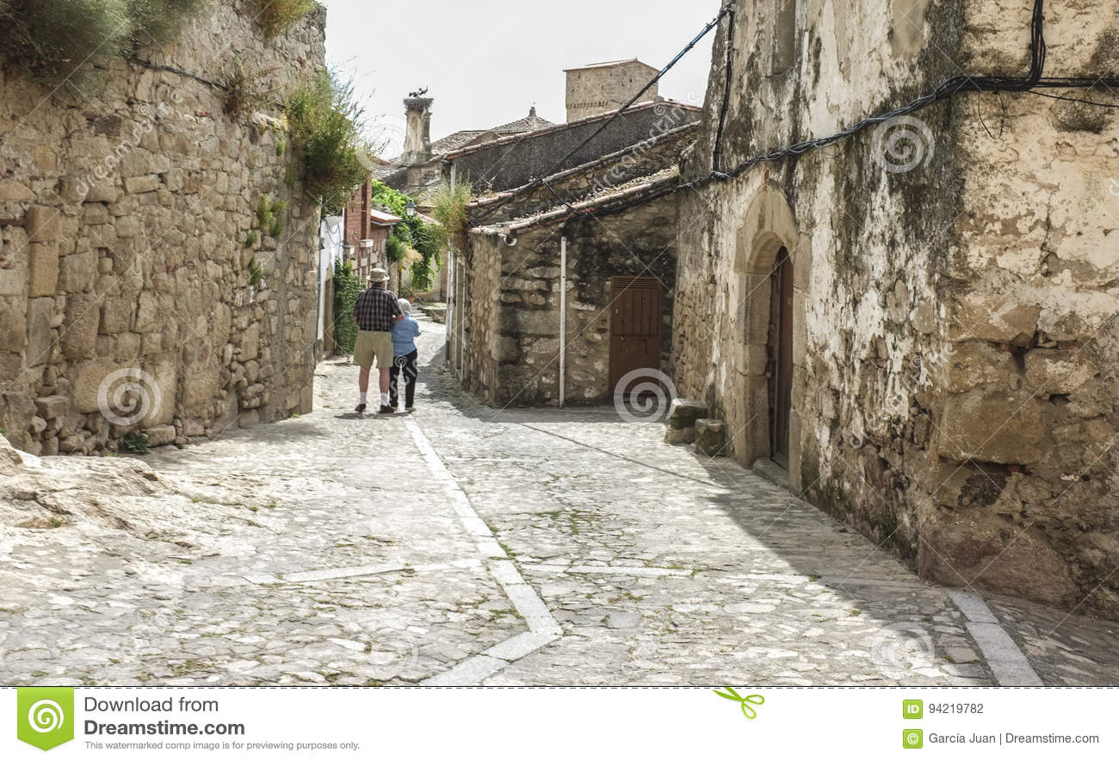 走在中世纪街道的资深夫妇在特鲁希略角,西班牙