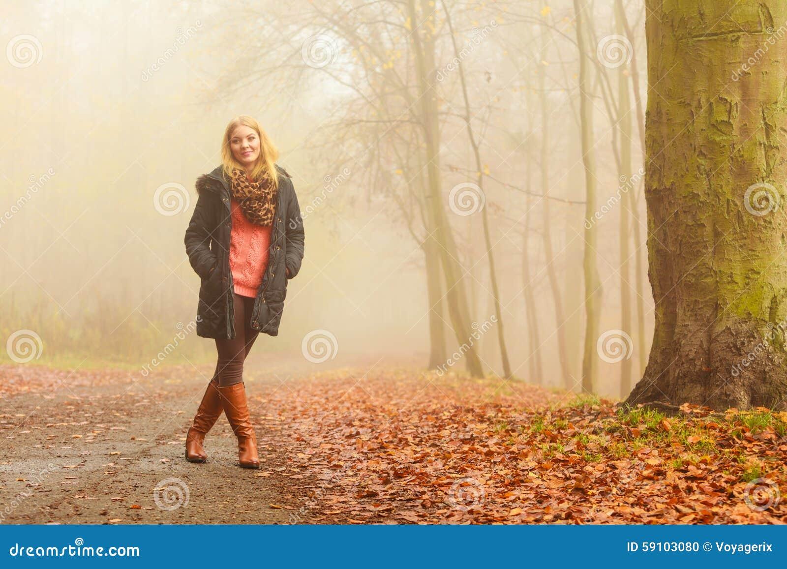 走在公园的妇女在有雾的天