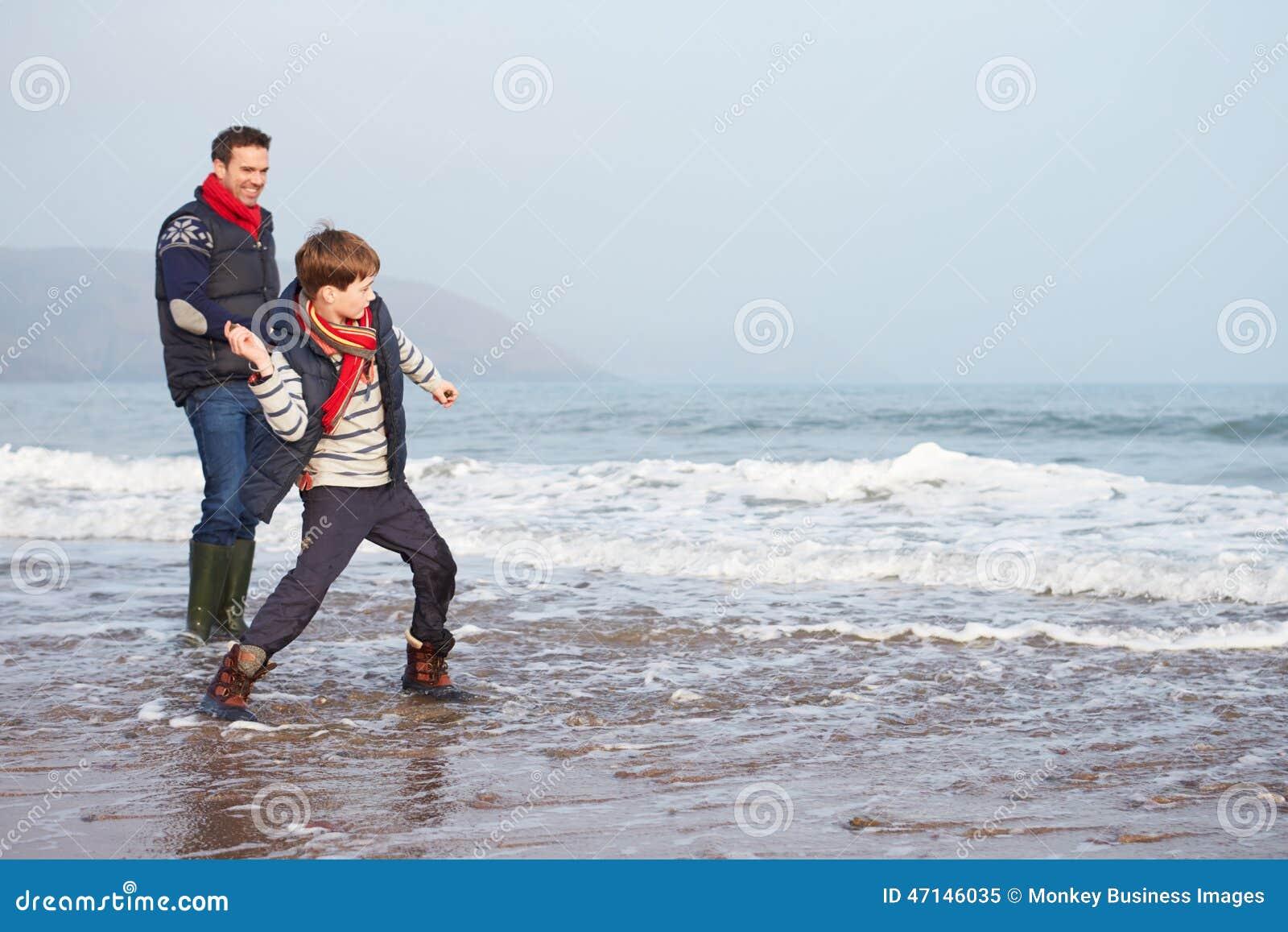 走在冬天海滩和投掷的石头的父亲和儿子