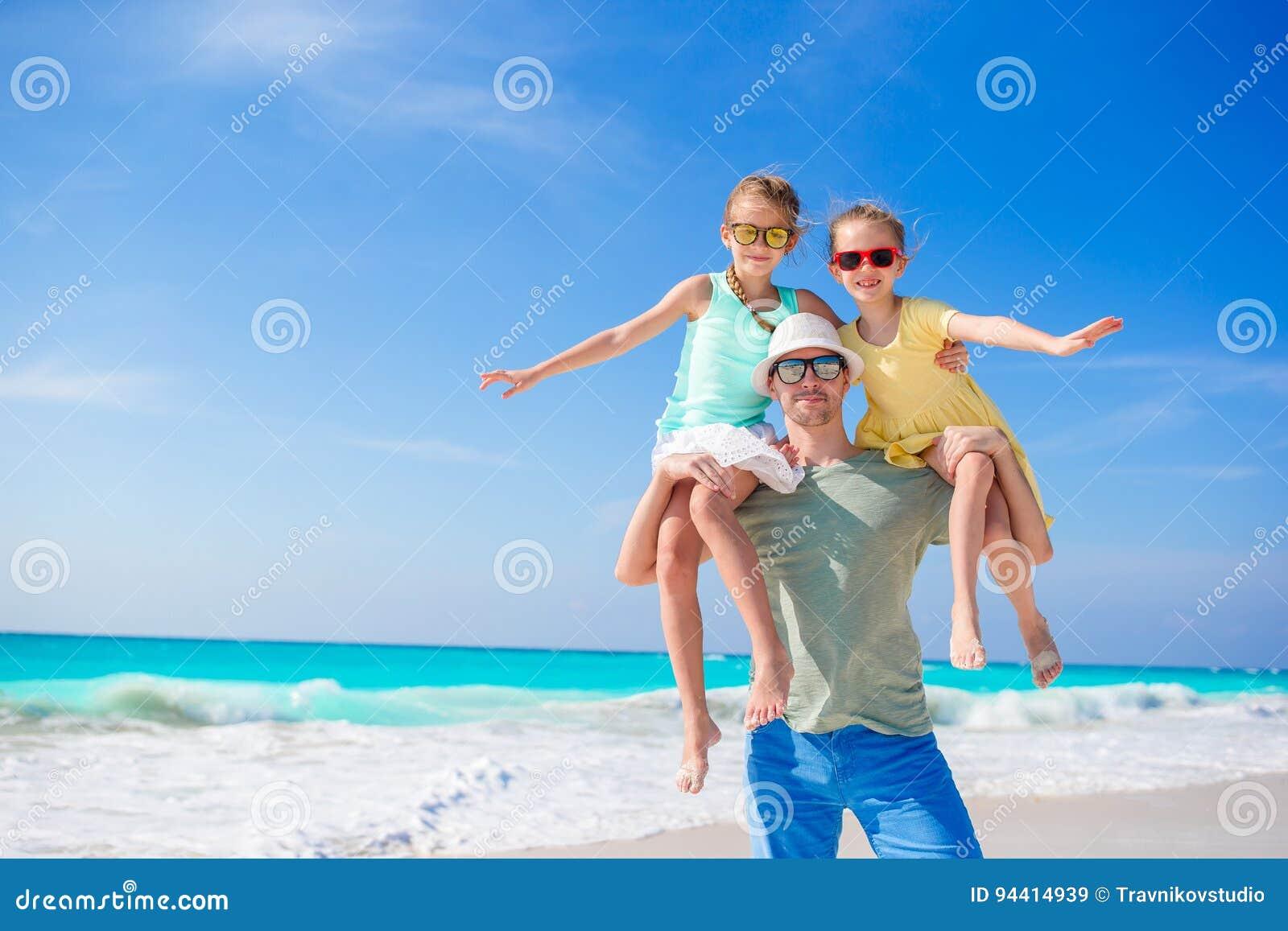 走在加勒比岛上的白色热带海滩的爸爸家庭和孩子获得很多乐趣
