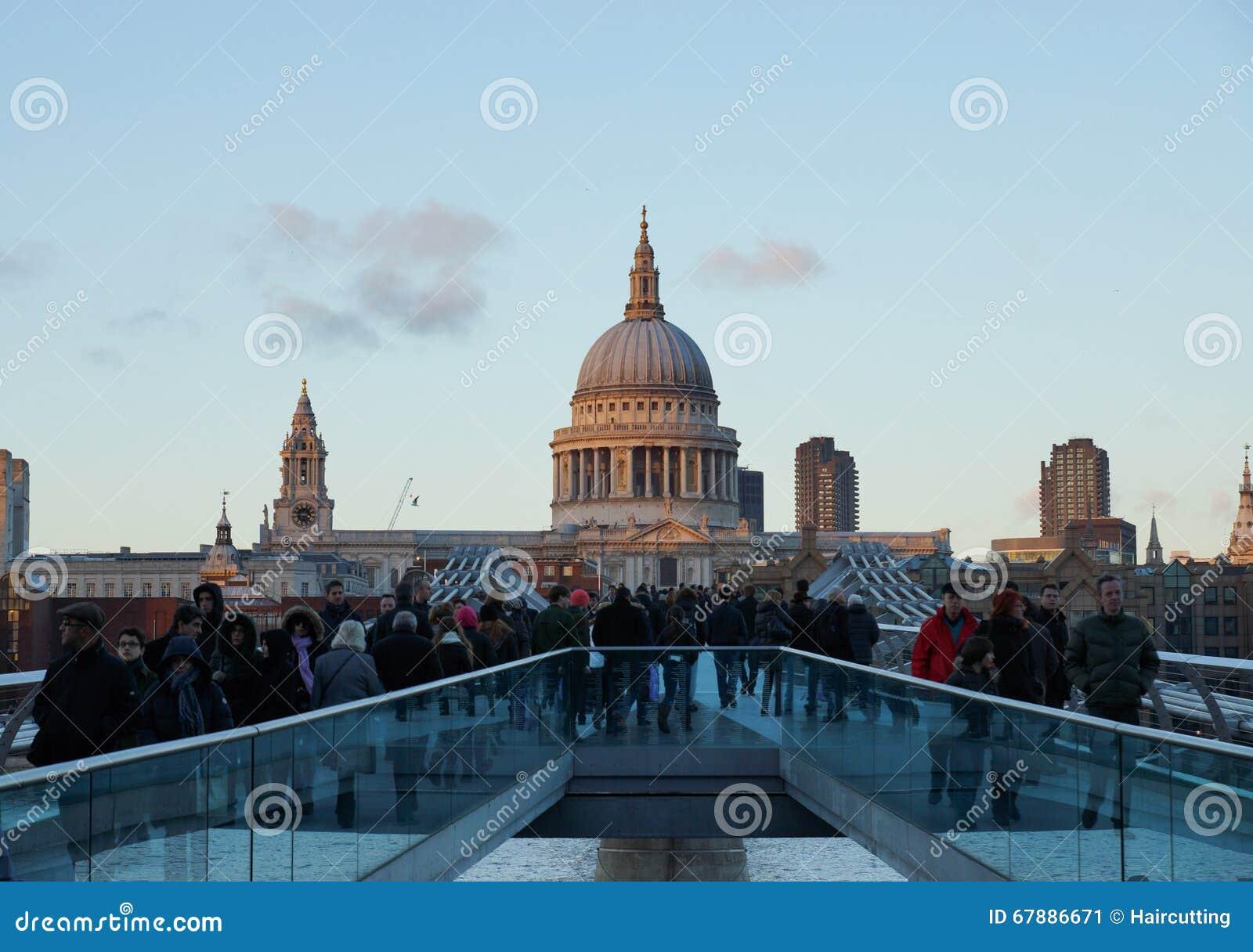 走在千年桥梁在黄昏,伦敦,英国的人们