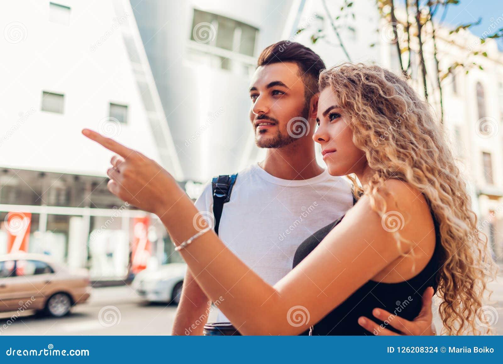走在城市的游人混合的族种夫妇  阿拉伯男人和白人妇女去的购物