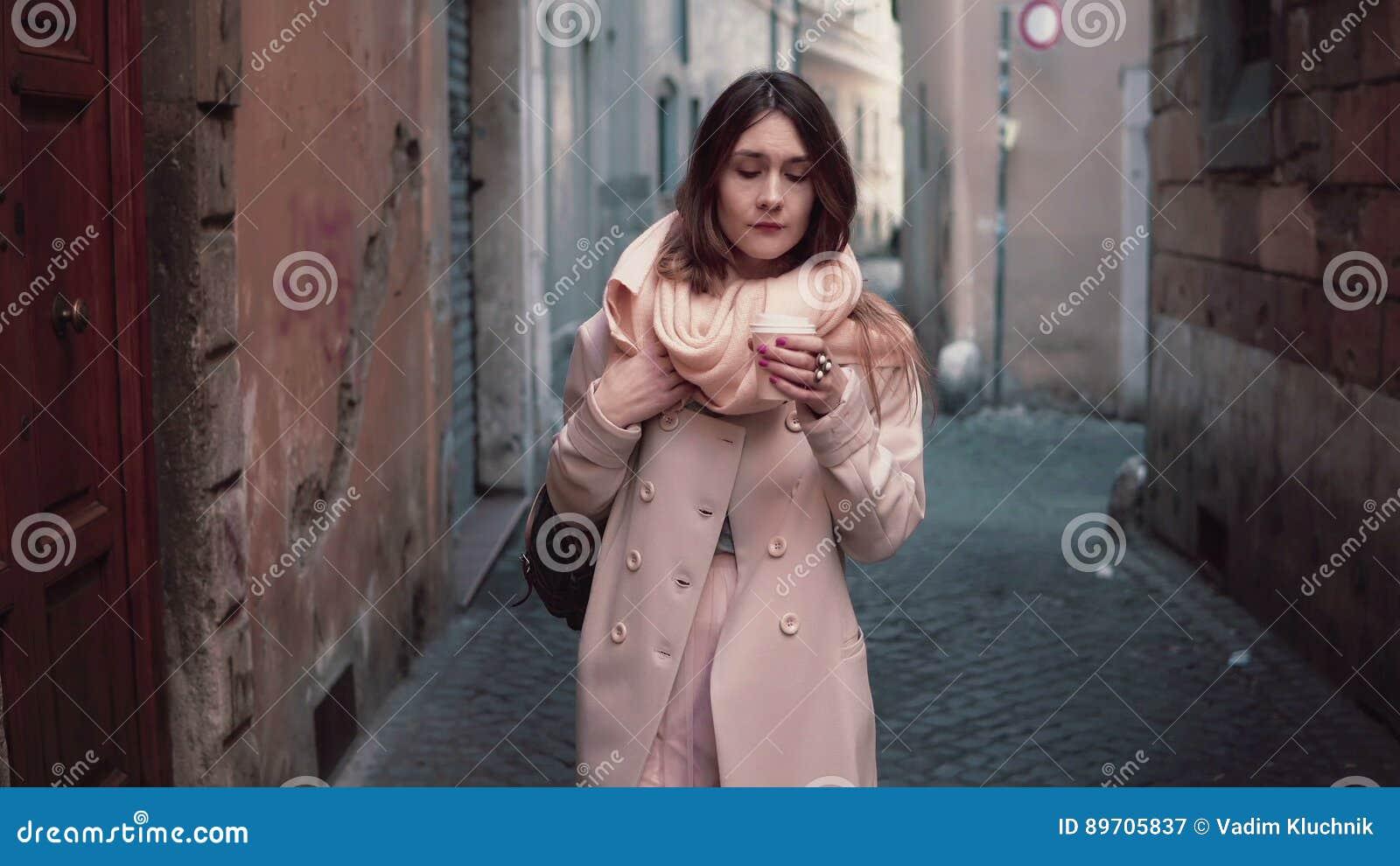走在城市的年轻美丽的时髦的女人画象  女孩去工作在早晨和饮用的咖啡
