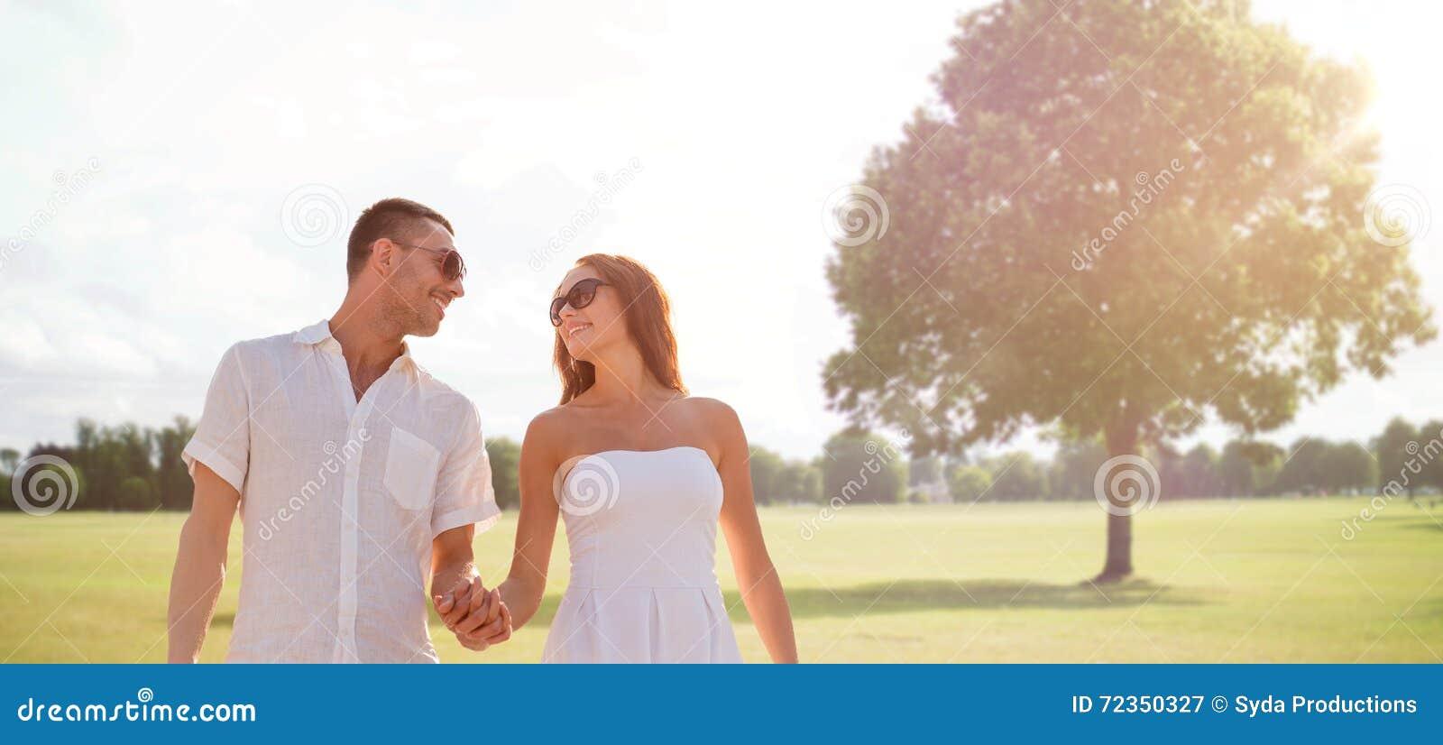 走在夏天公园的愉快的微笑的夫妇