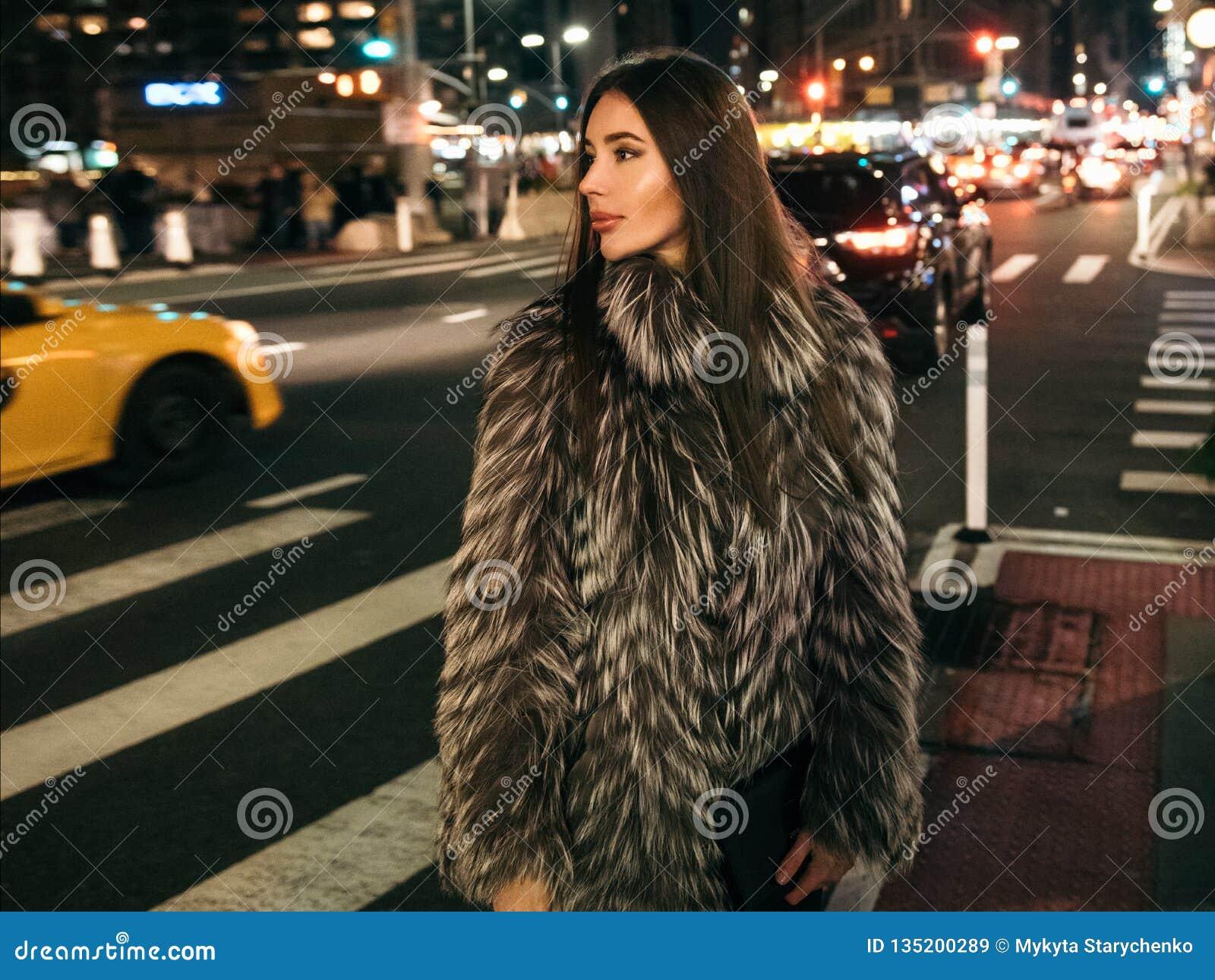 走在夜城市街道上的华美的端庄的妇女穿假毛皮夹克和拿着看对边的袋子