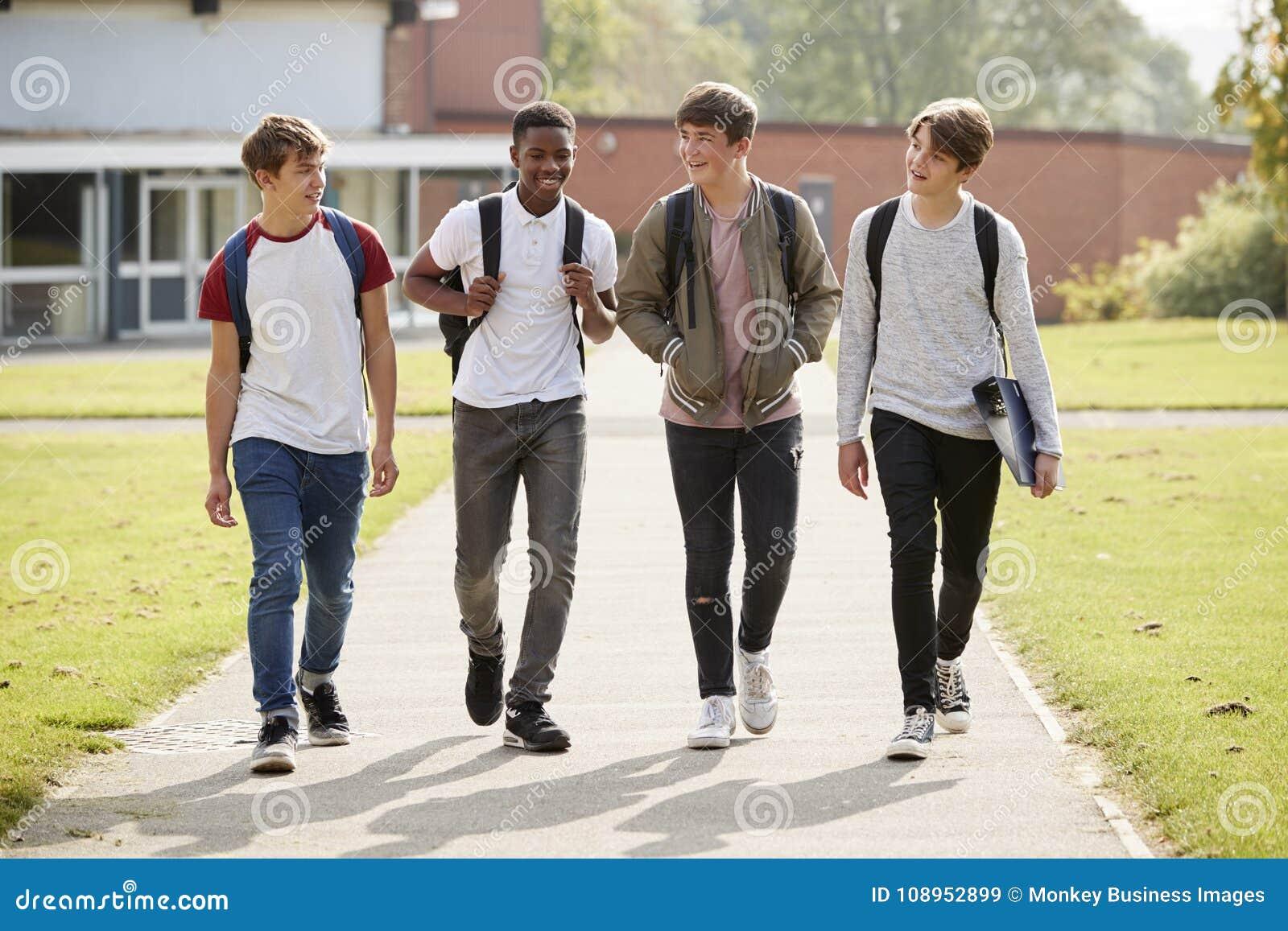 走在学院校园附近的小组男性少年学生