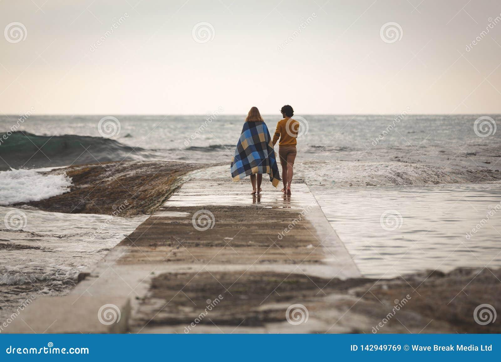 走在岩石的白种人夫妇在海滩附近