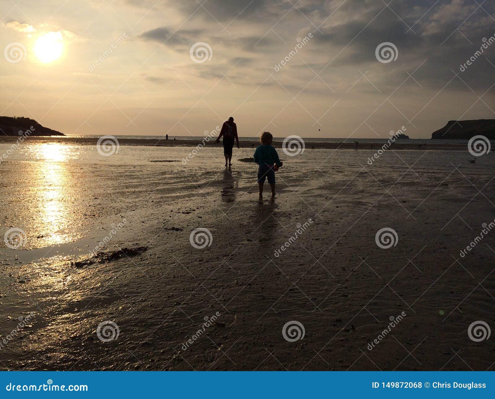 走在日落海滩的女孩和母亲