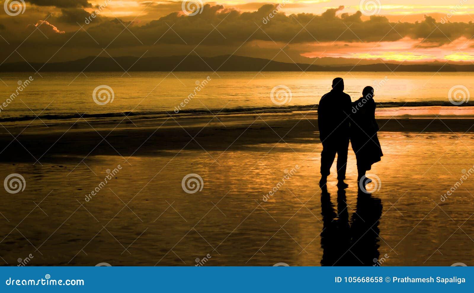 走在日落的一个海滩的年长夫妇