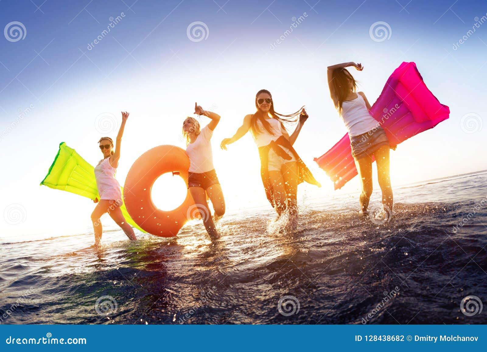 走在日落的愉快的女孩浇灌与游泳床垫