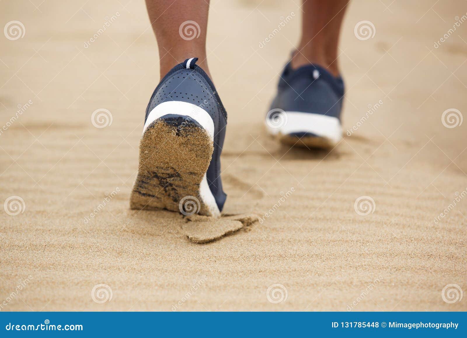 走在沙子的低角度女性鞋子