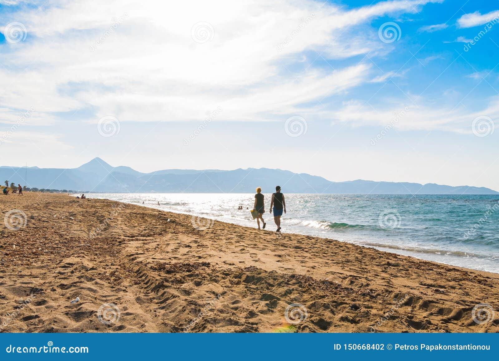 走在海滩的两人由横跨海岸好日子天空清晰步行的海