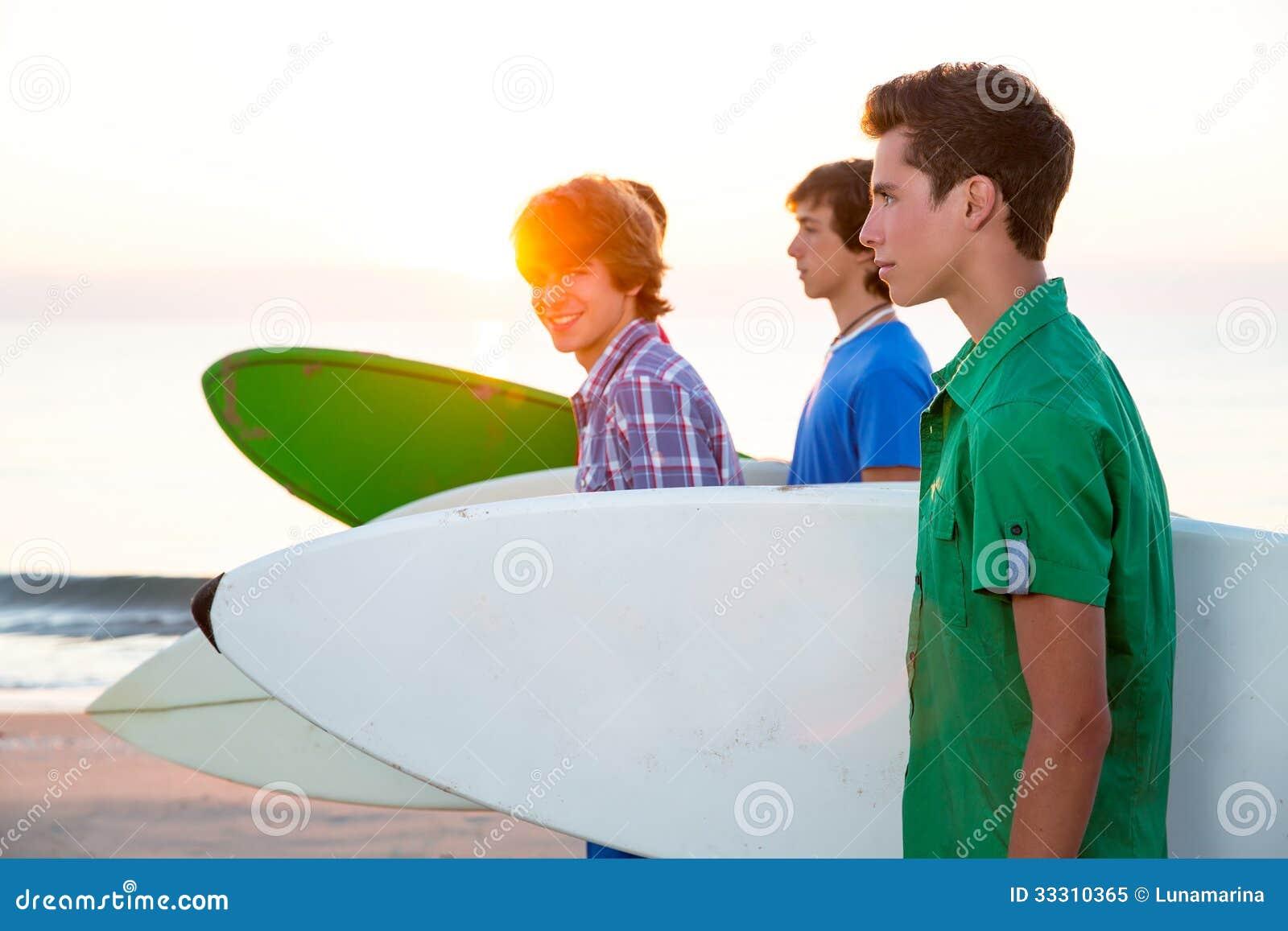 走在海滩岸的冲浪者青少年的男孩
