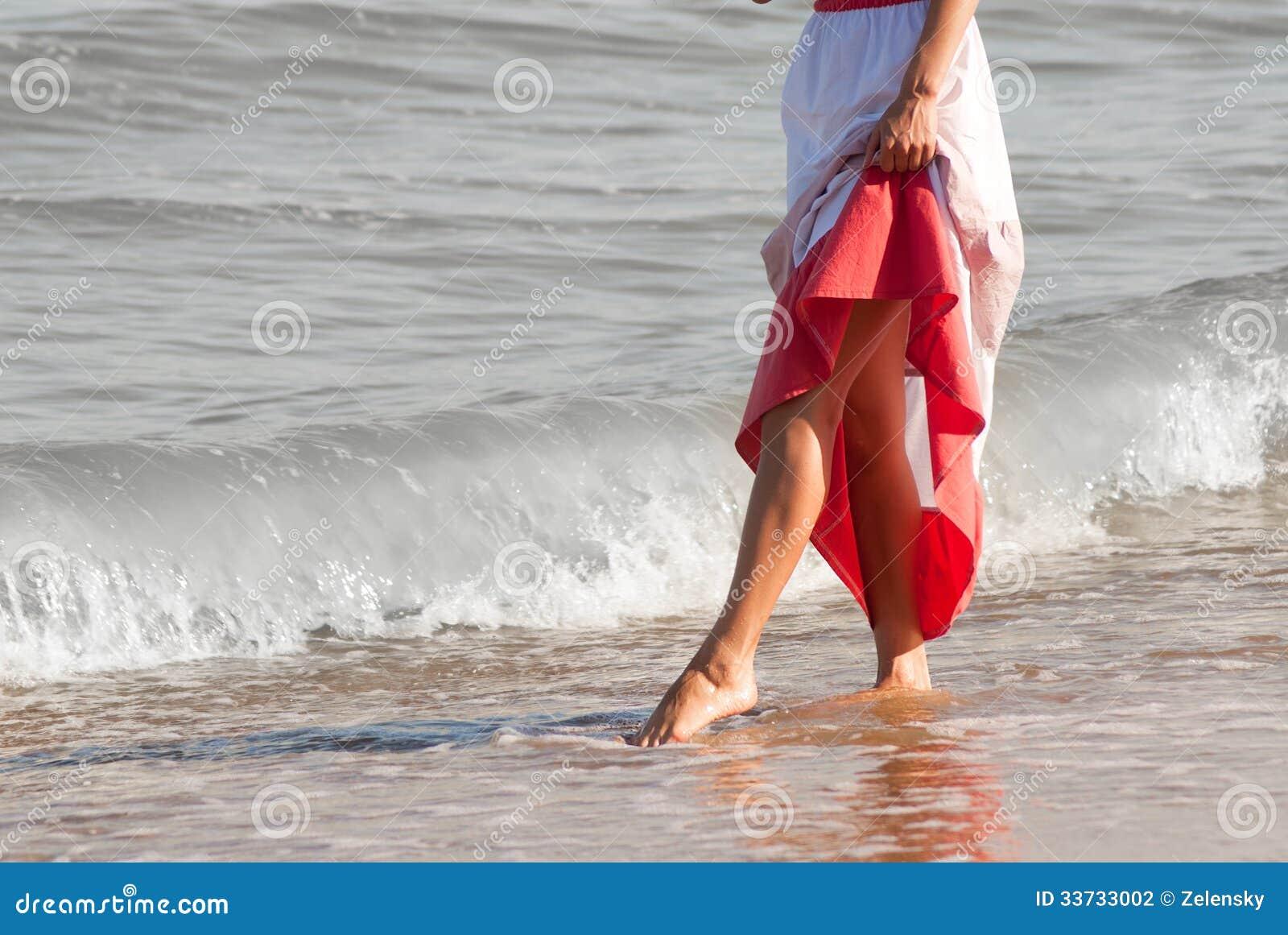 走在海滩的单独妇女