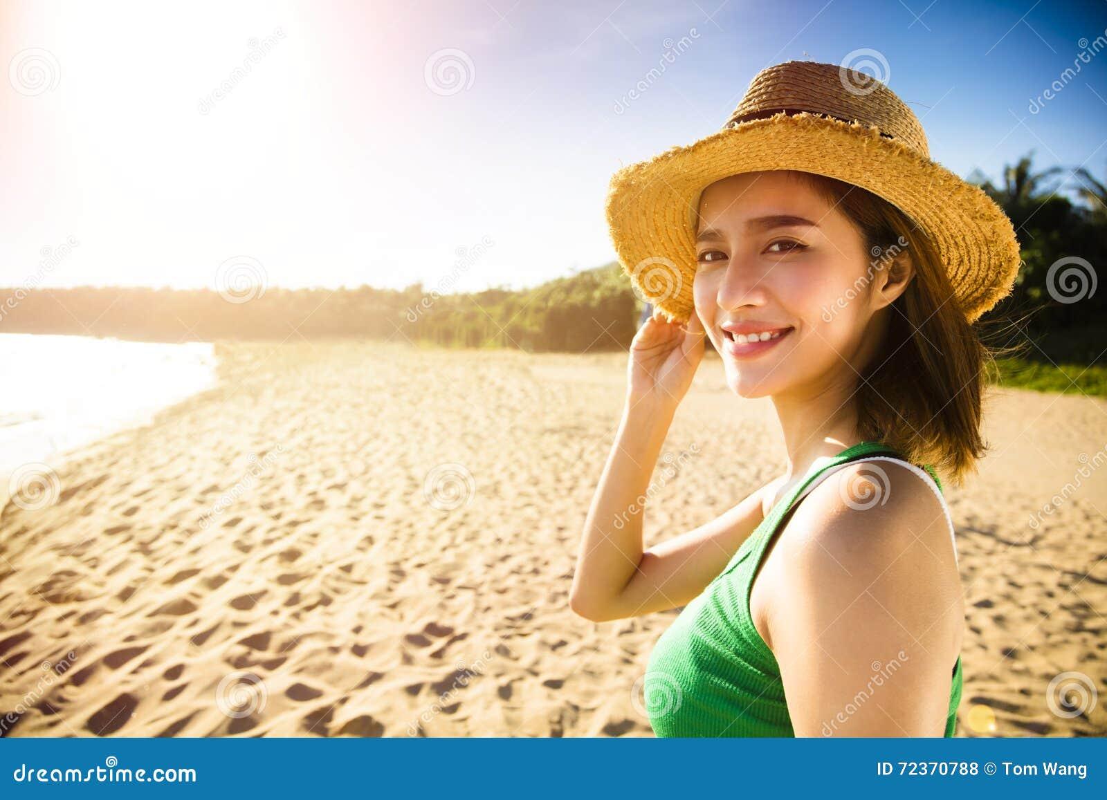 走在海滩的少妇在日落