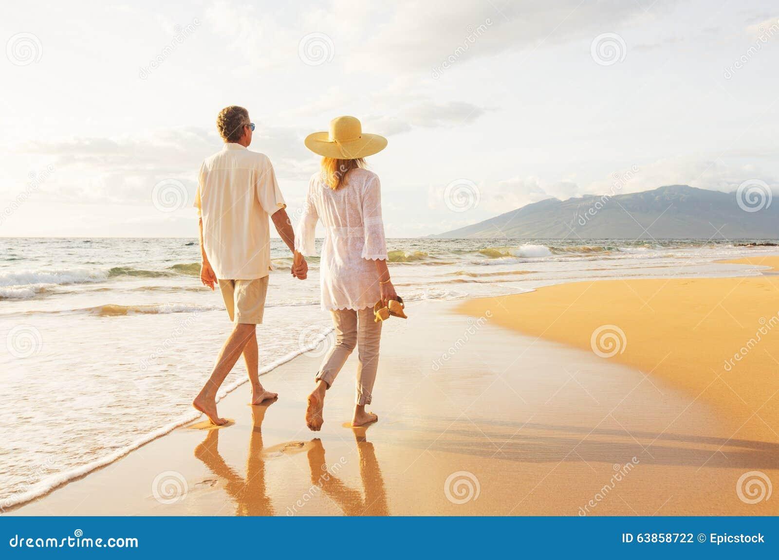走在海滩的成熟夫妇在日落