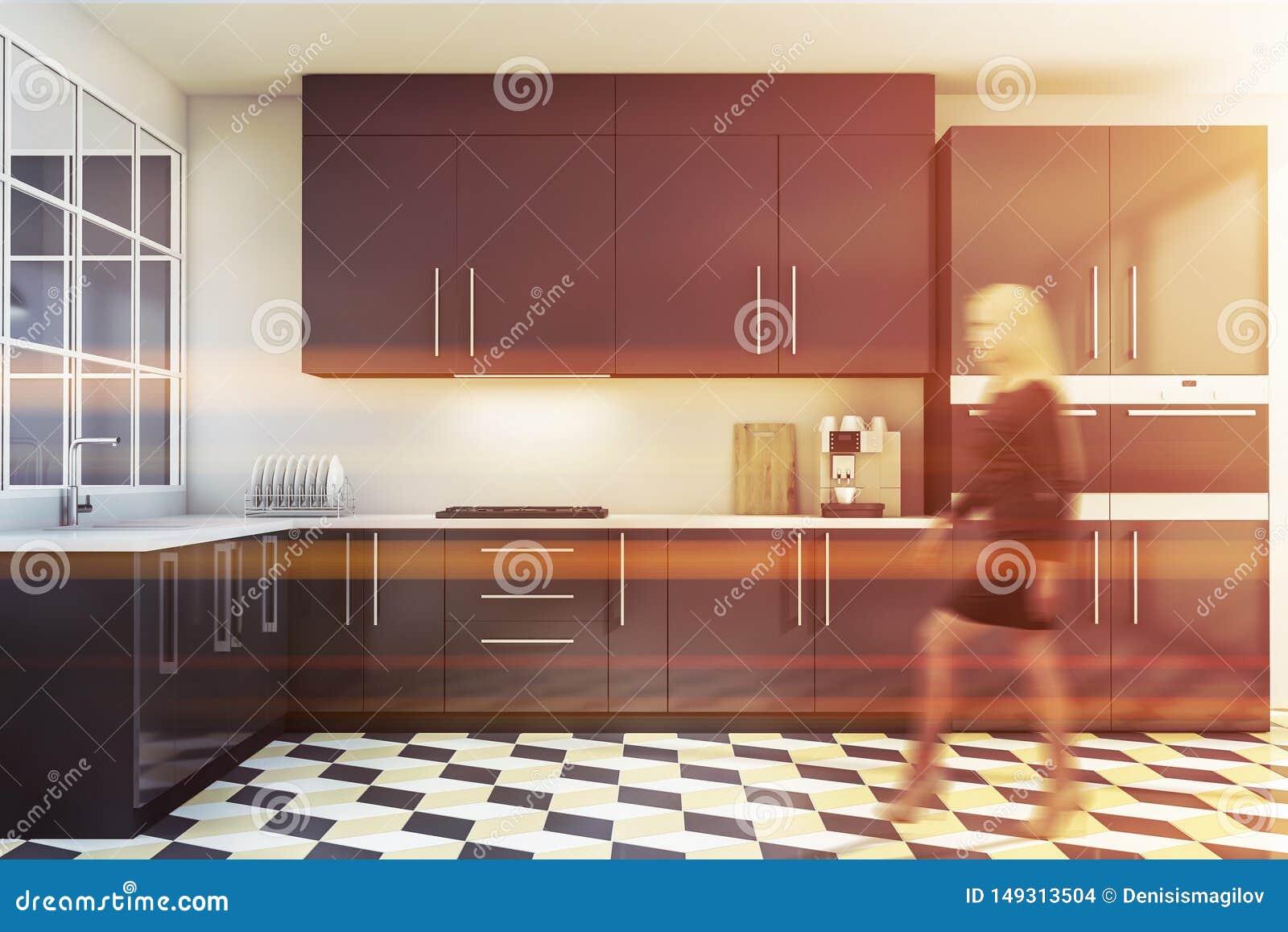 走在白色和灰色厨房里的白肤金发的妇女