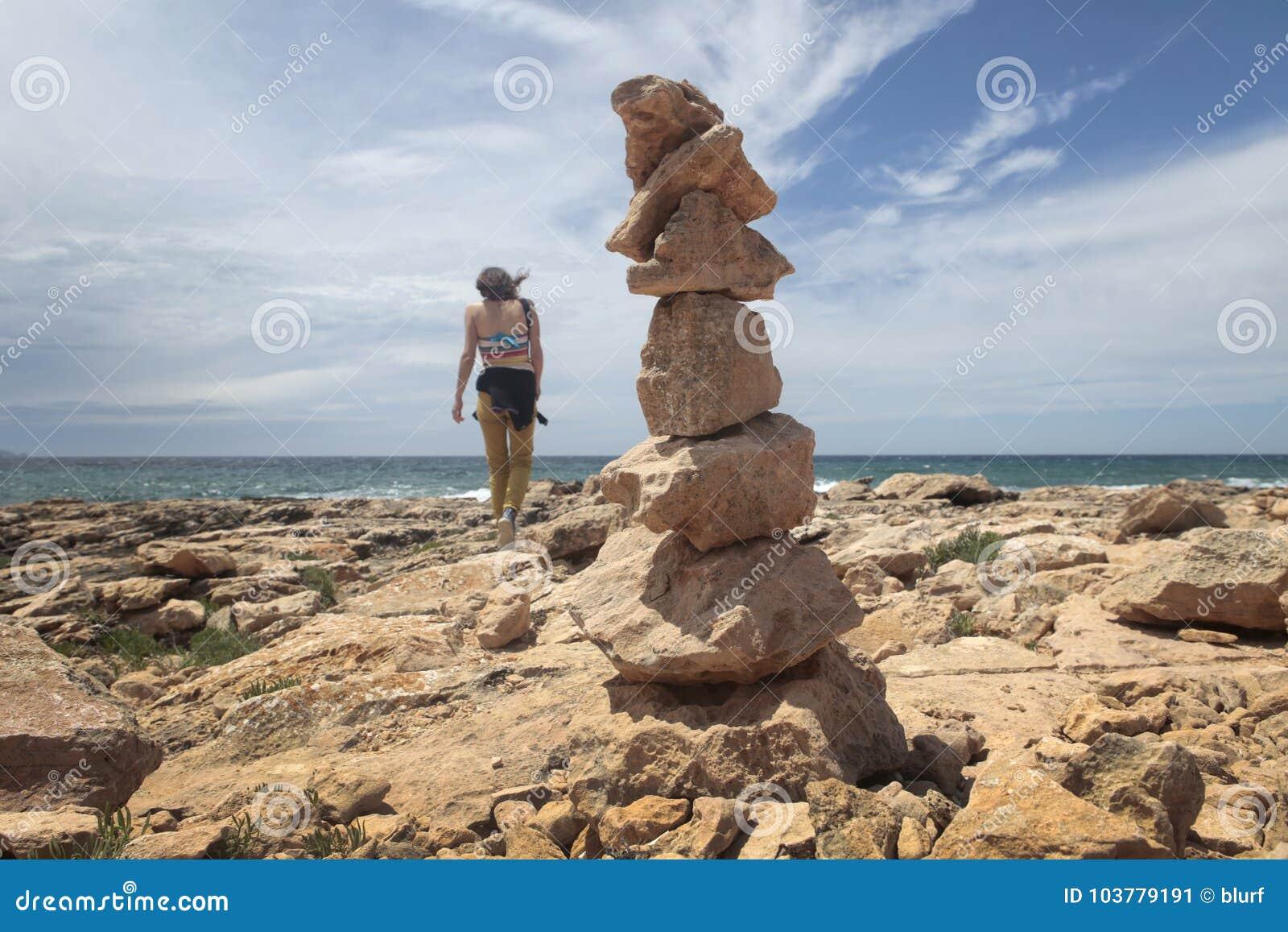 走在石头旁边的女孩在majorca海岛的南海岸登上