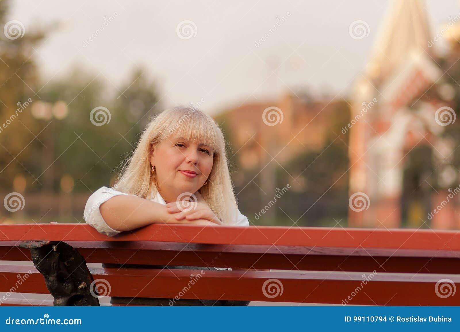 走在秋天公园的资深女商人 一个经典衣物样式的一名妇女 服装的端庄的妇女