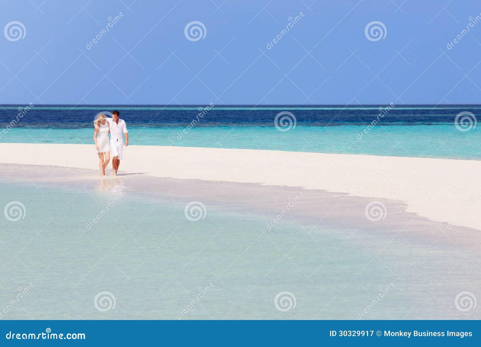 走在美丽的热带海滩的浪漫夫妇