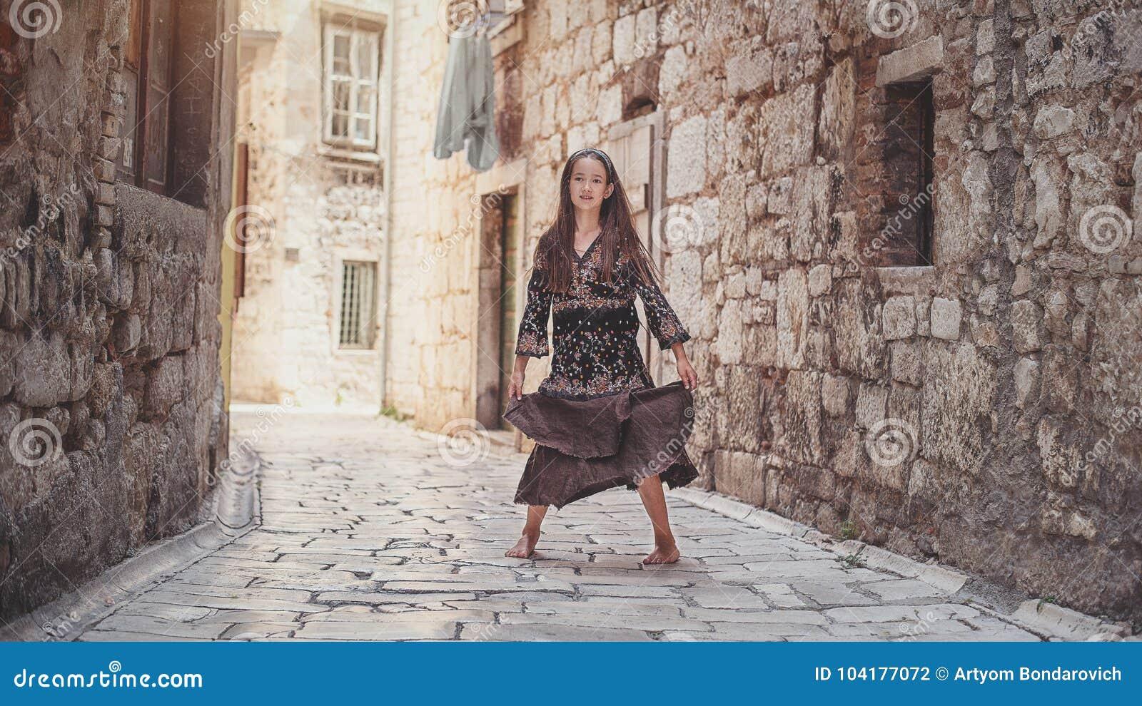 走在老镇的逗人喜爱的女孩 好女孩在中世纪城市