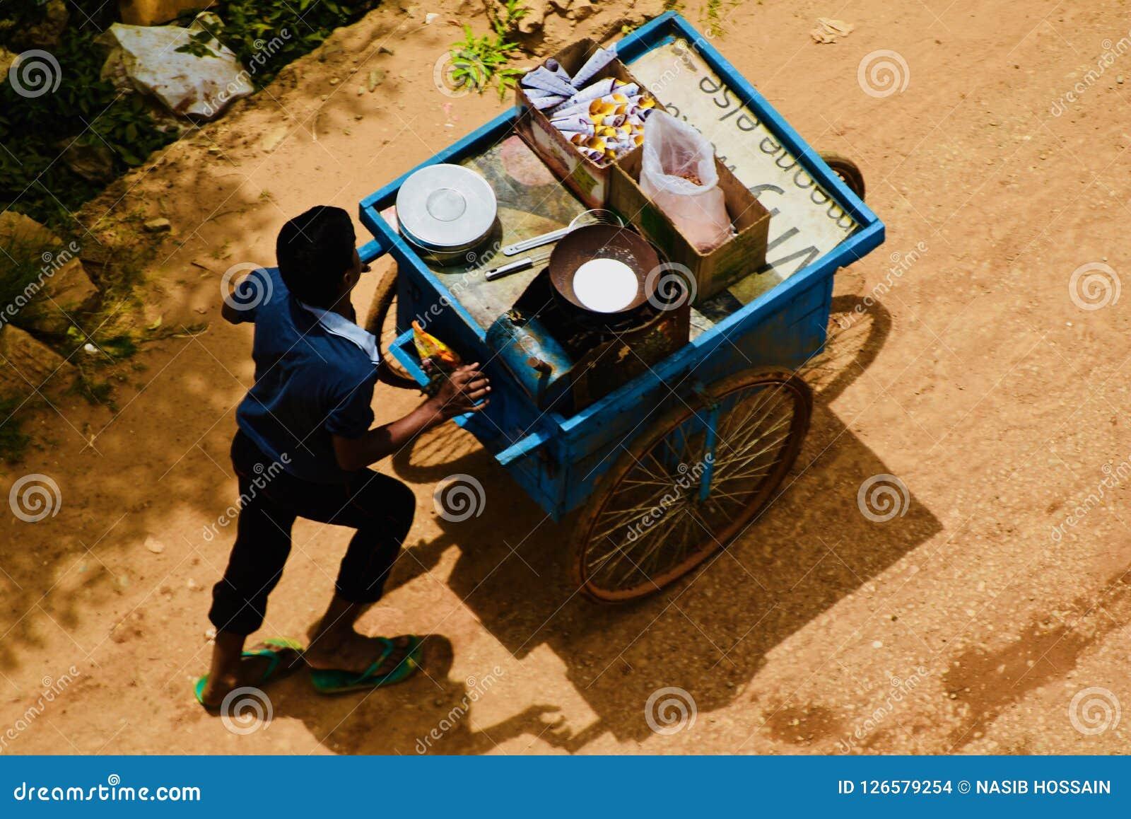走在路的一位年轻街道食物卖主在班格洛 库存图片