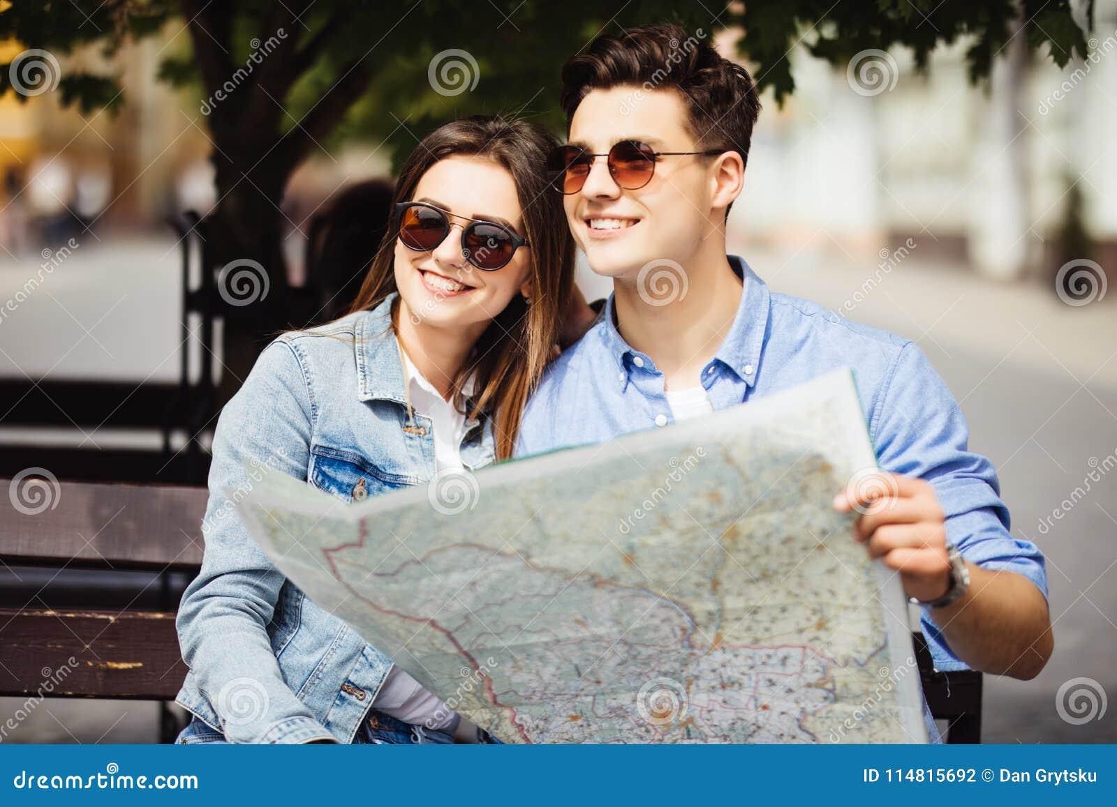 走愉快的夫妇户外观光和拿着一张地图在新的城市 汽车城市概念都伯林映射小的旅行