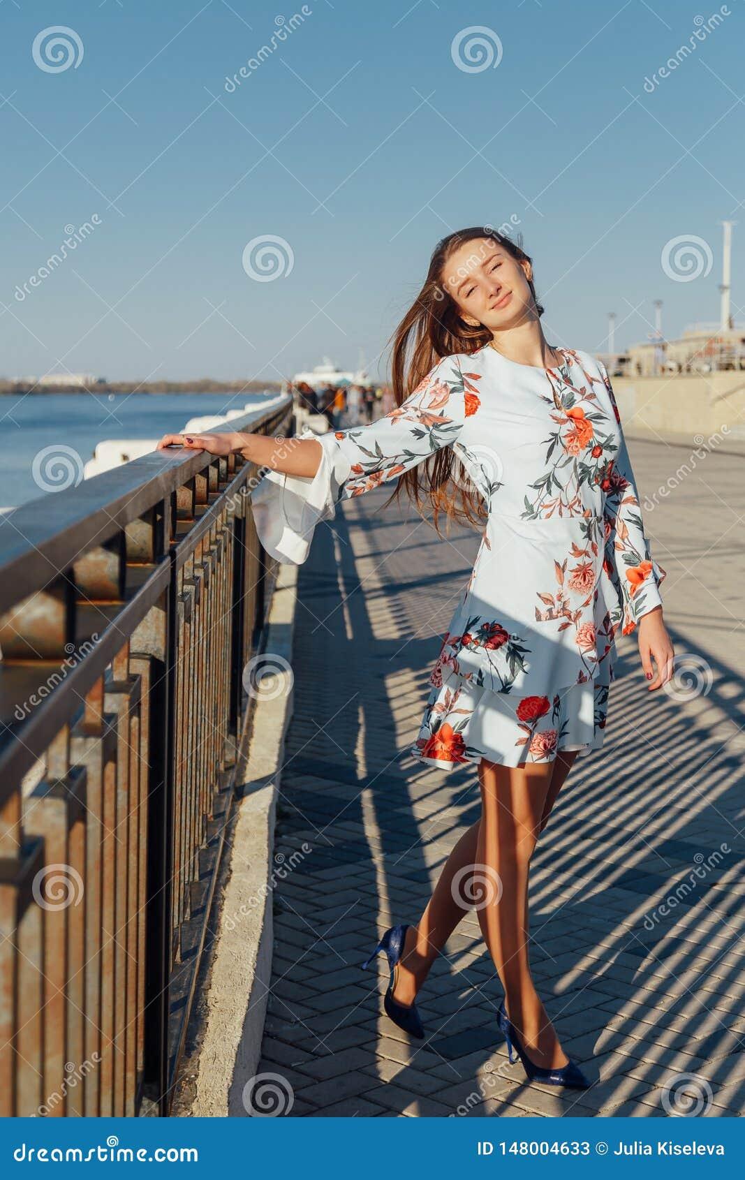 走沿城市的江边的一年轻美女的动态时尚样式画象