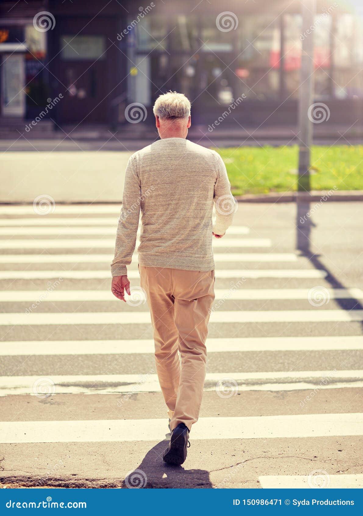 走沿城市行人穿越道的老人