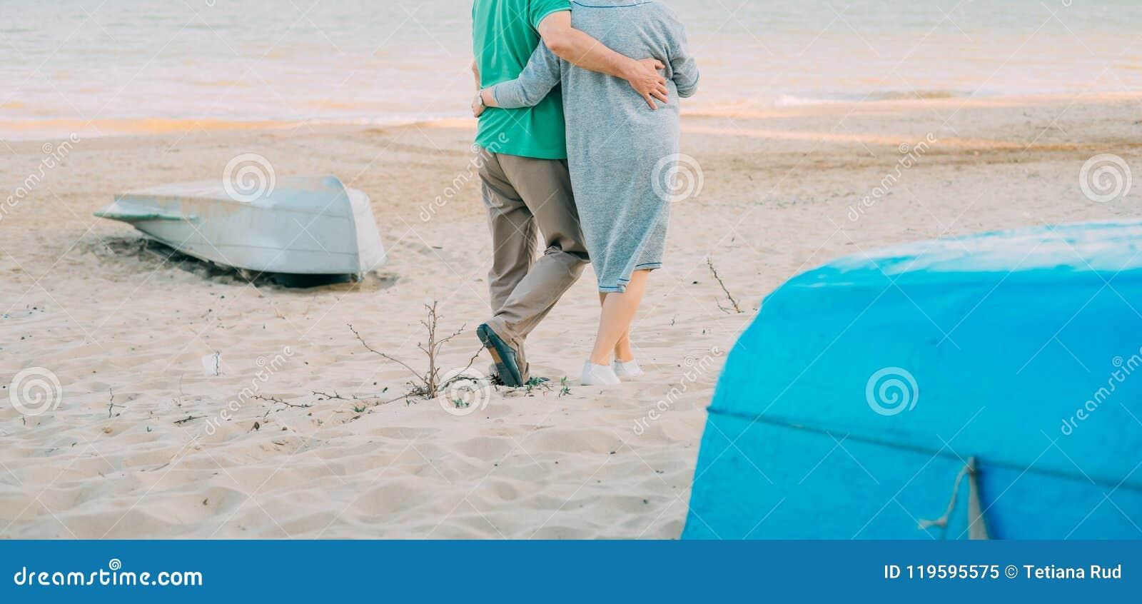 走沿海岸的浪漫资深夫妇室外射击握手 走在海滩togeth的老人和妇女