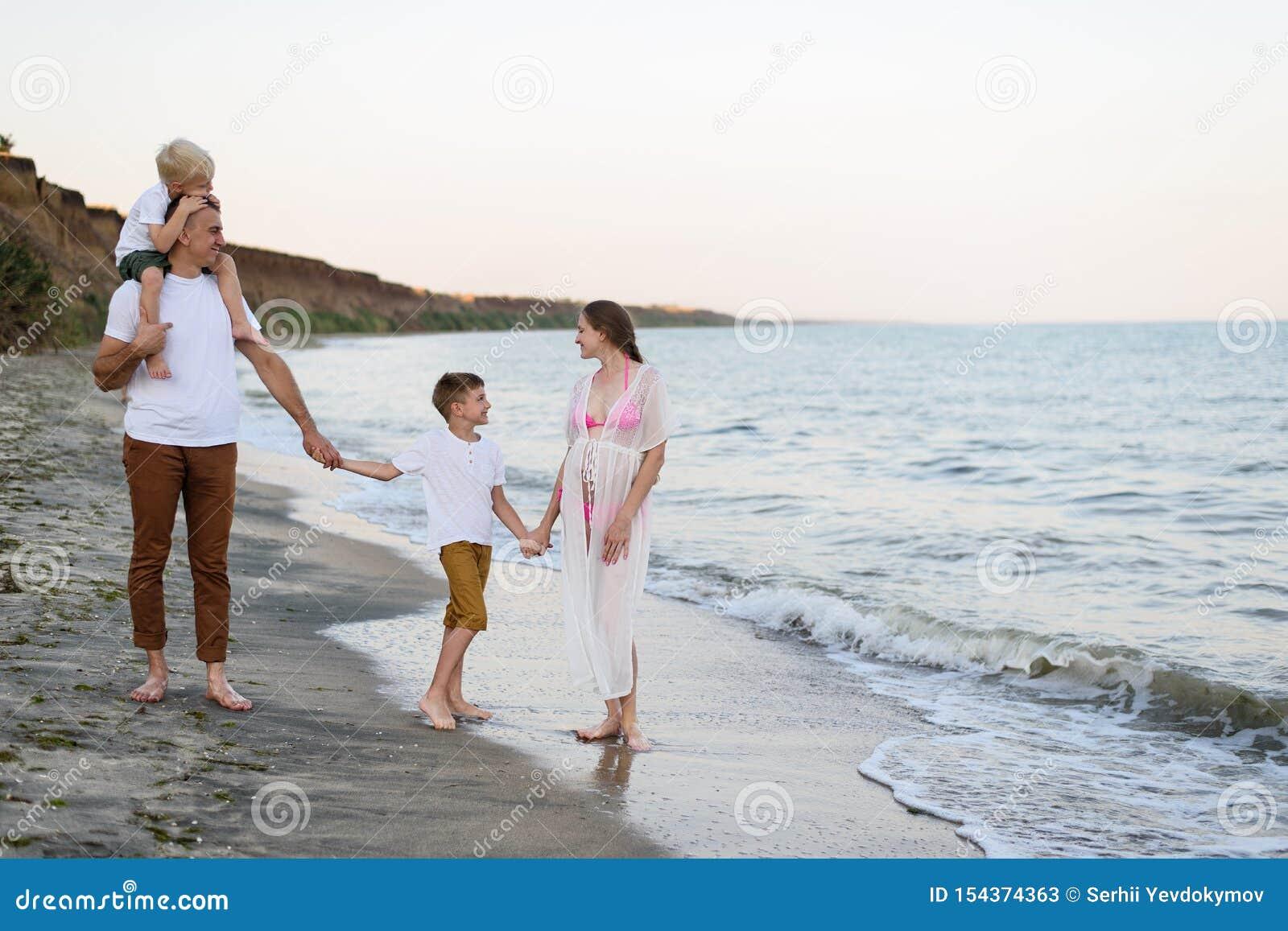 走沿海滨的四口之家 父母和两个儿子 愉快的友好的家庭